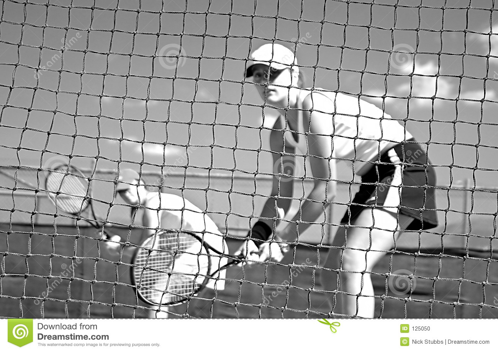 Giocatori di tennis della donna che esaminano macchina fotografica attraverso la rete che attende per giocare mentre esaminando ma