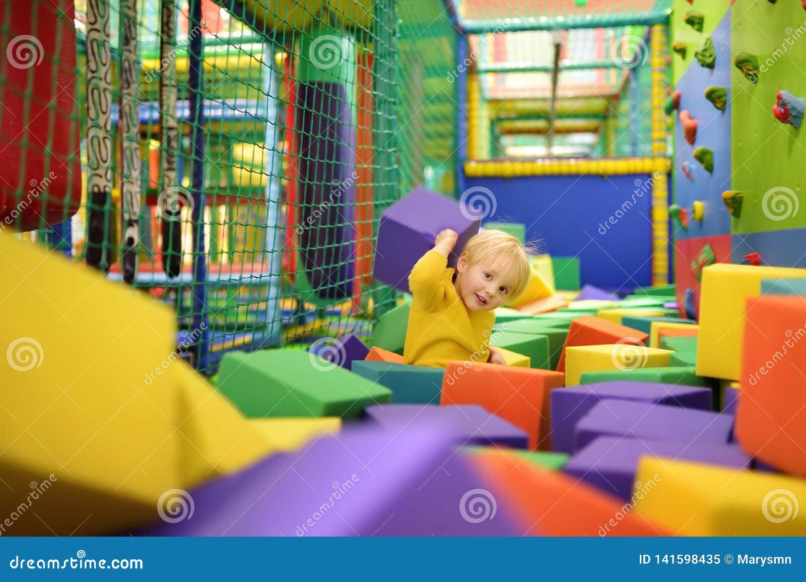 Giochi svegli del ragazzino con i cubi molli nello stagno asciutto nel centro del gioco Bambino che gioca sul campo da giuoco del