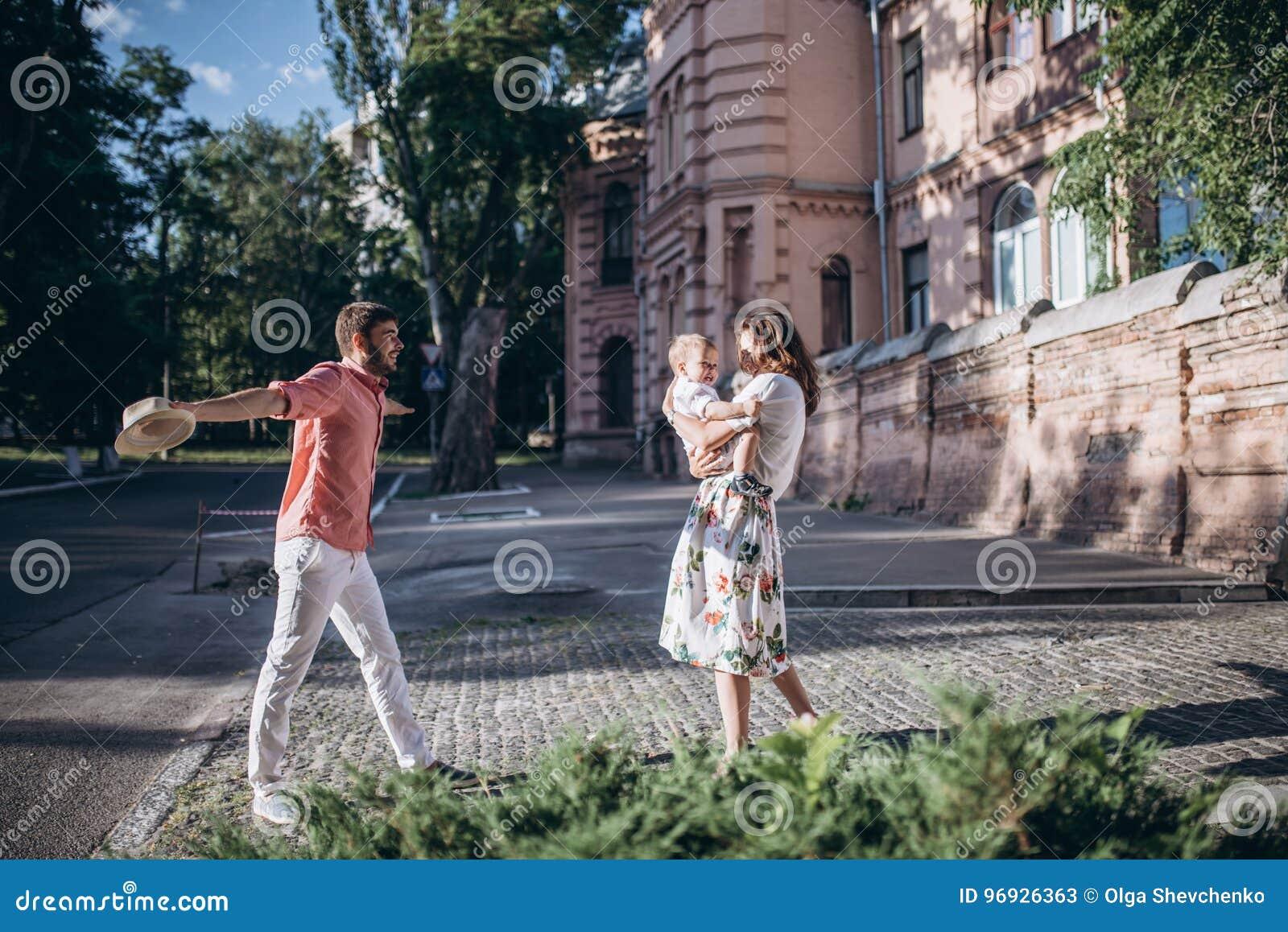Gioco alla moda felice dei genitori con il figlio Restano in via soleggiata di mattina, momento stupefacente della famiglia giorn