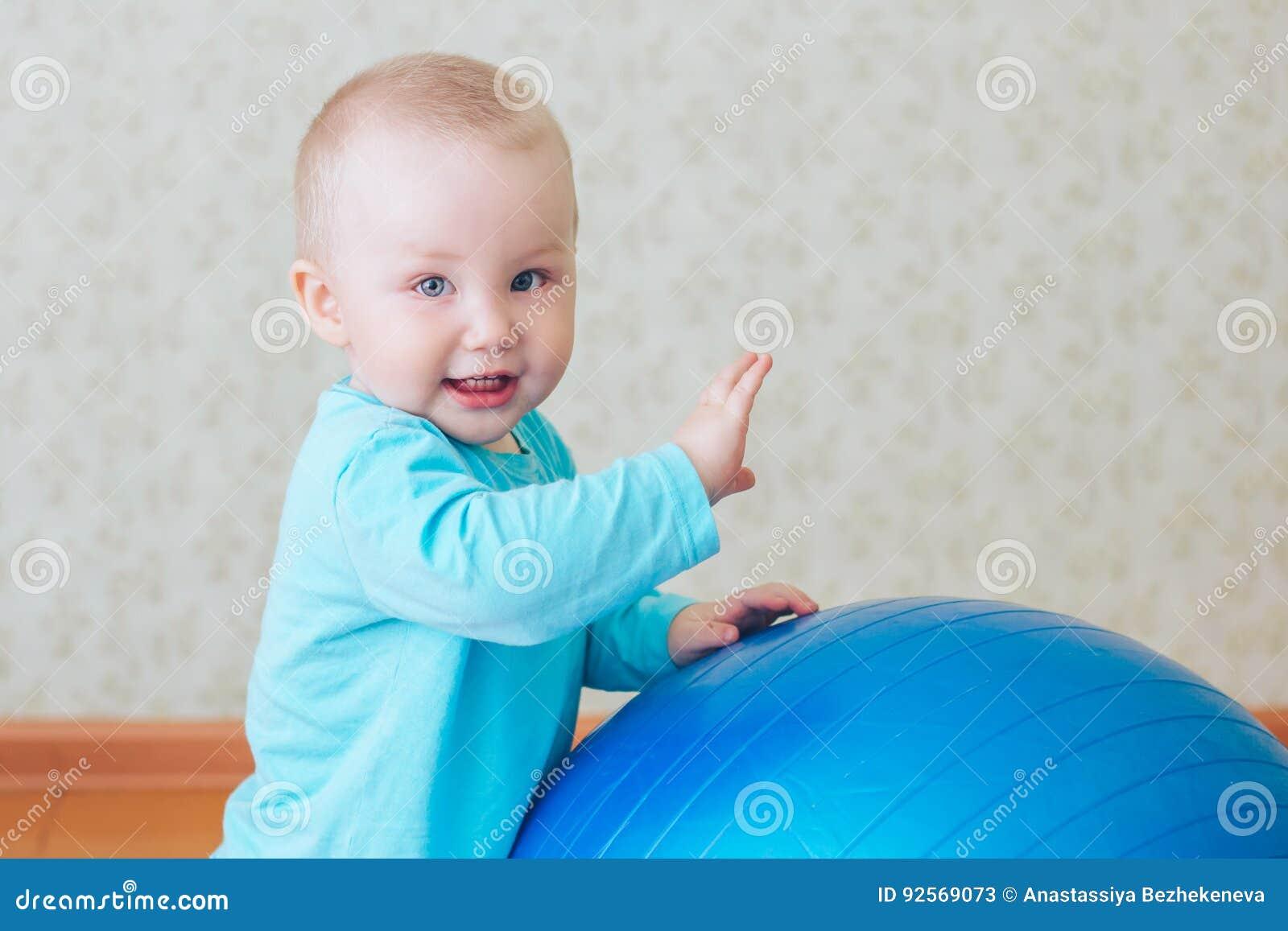 Gioco del bambino con la grande palla blu