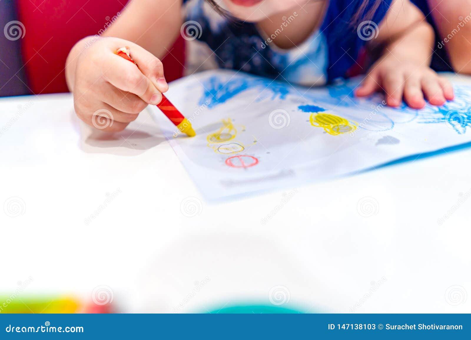 Gioco del bambino, studio ed imparare come colorare e disegnare il colore del pastello dentro alla carta con i suoi genitori