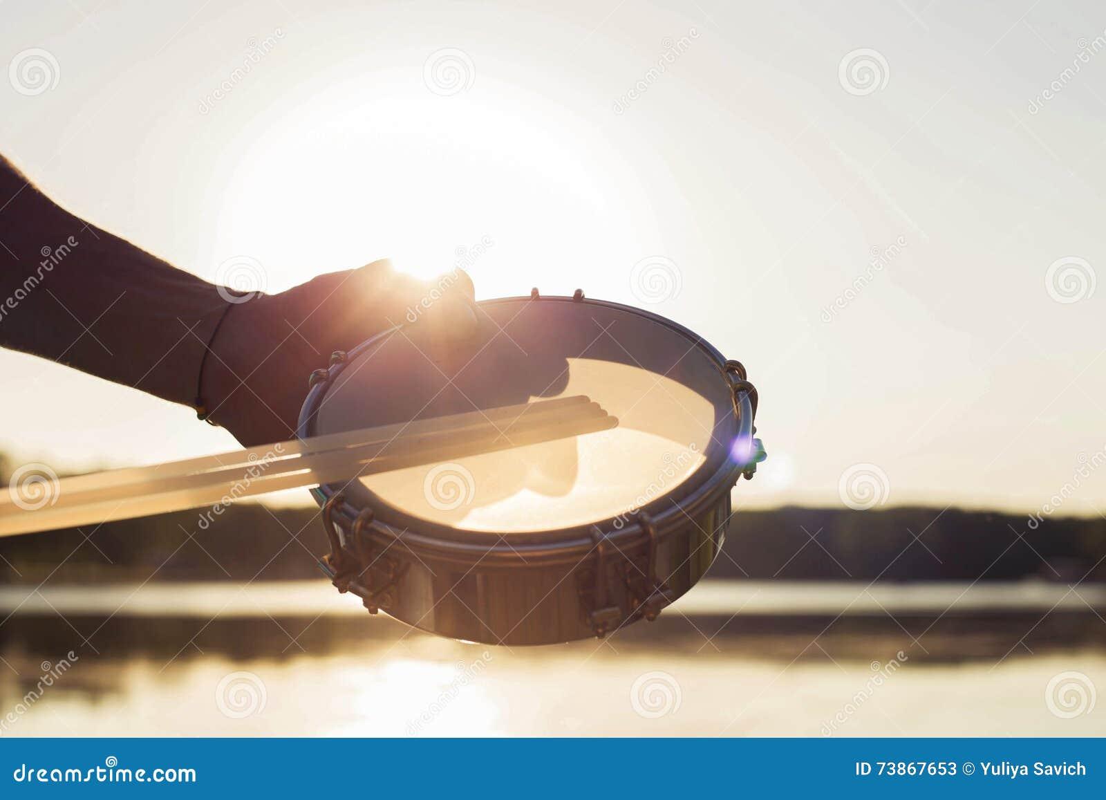 Gioco del tamburino dello strumento musicale sul cielo del fondo al tramonto