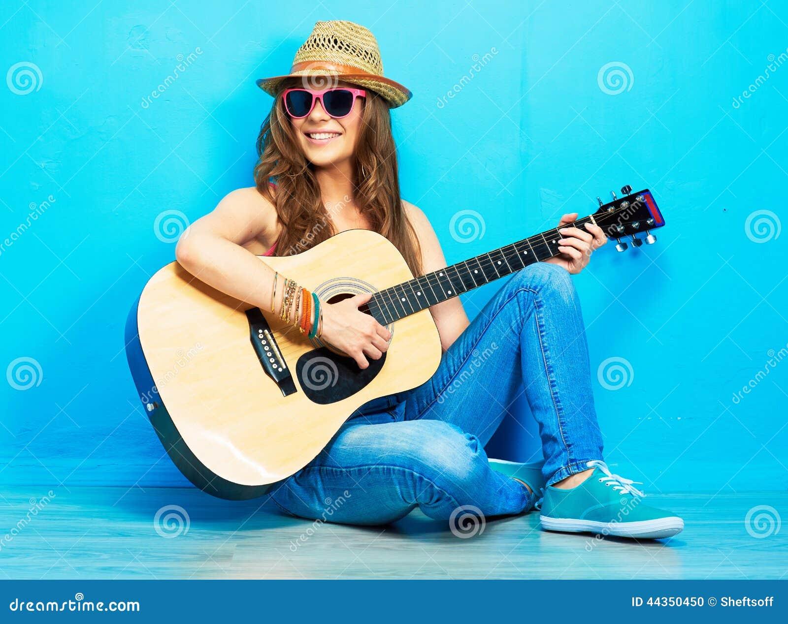 Gioco della chitarra della ragazza dell adolescente che si siede su un pavimento