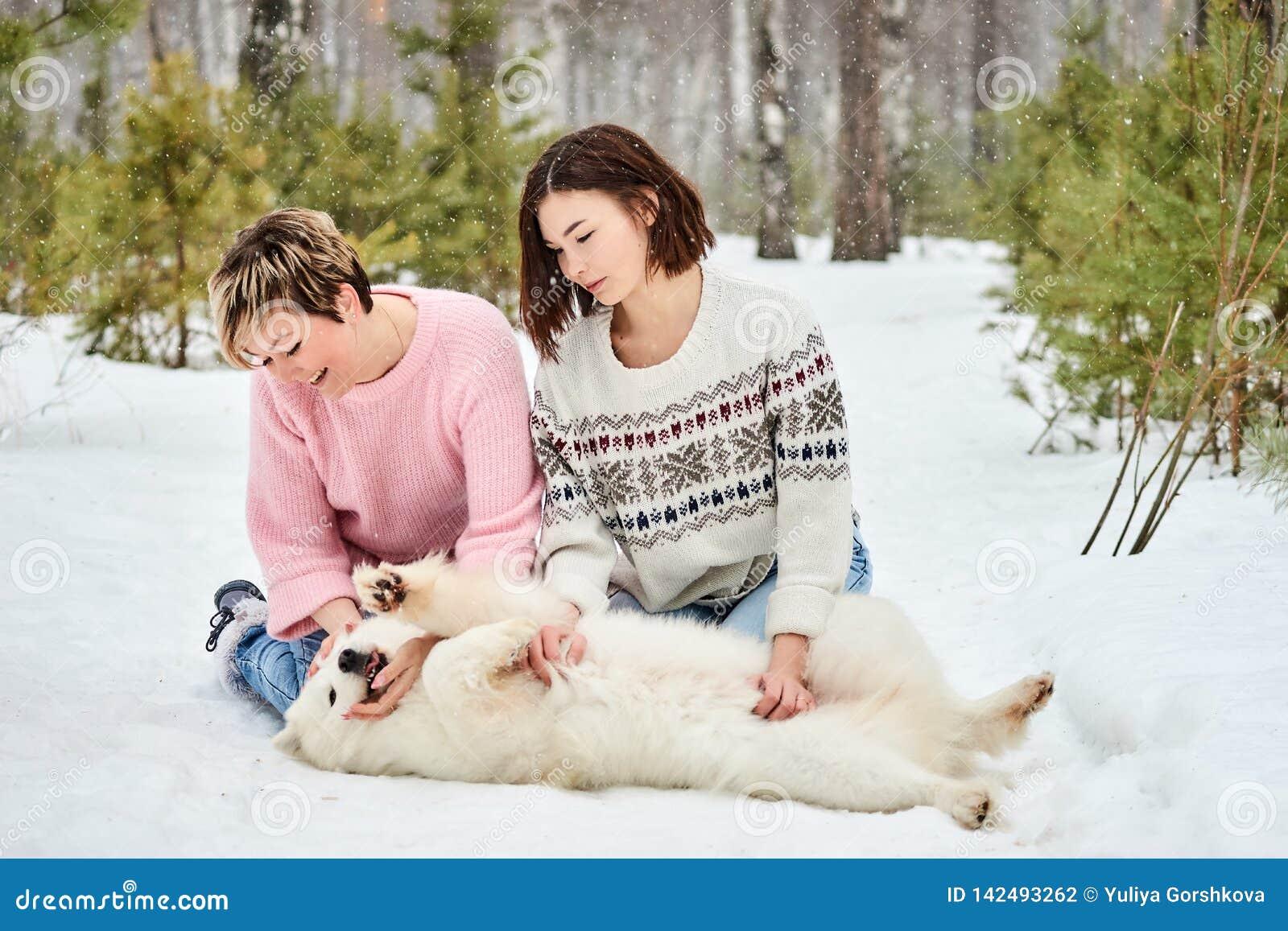 Gioco della figlia e della madre con il cane nell inverno la foresta