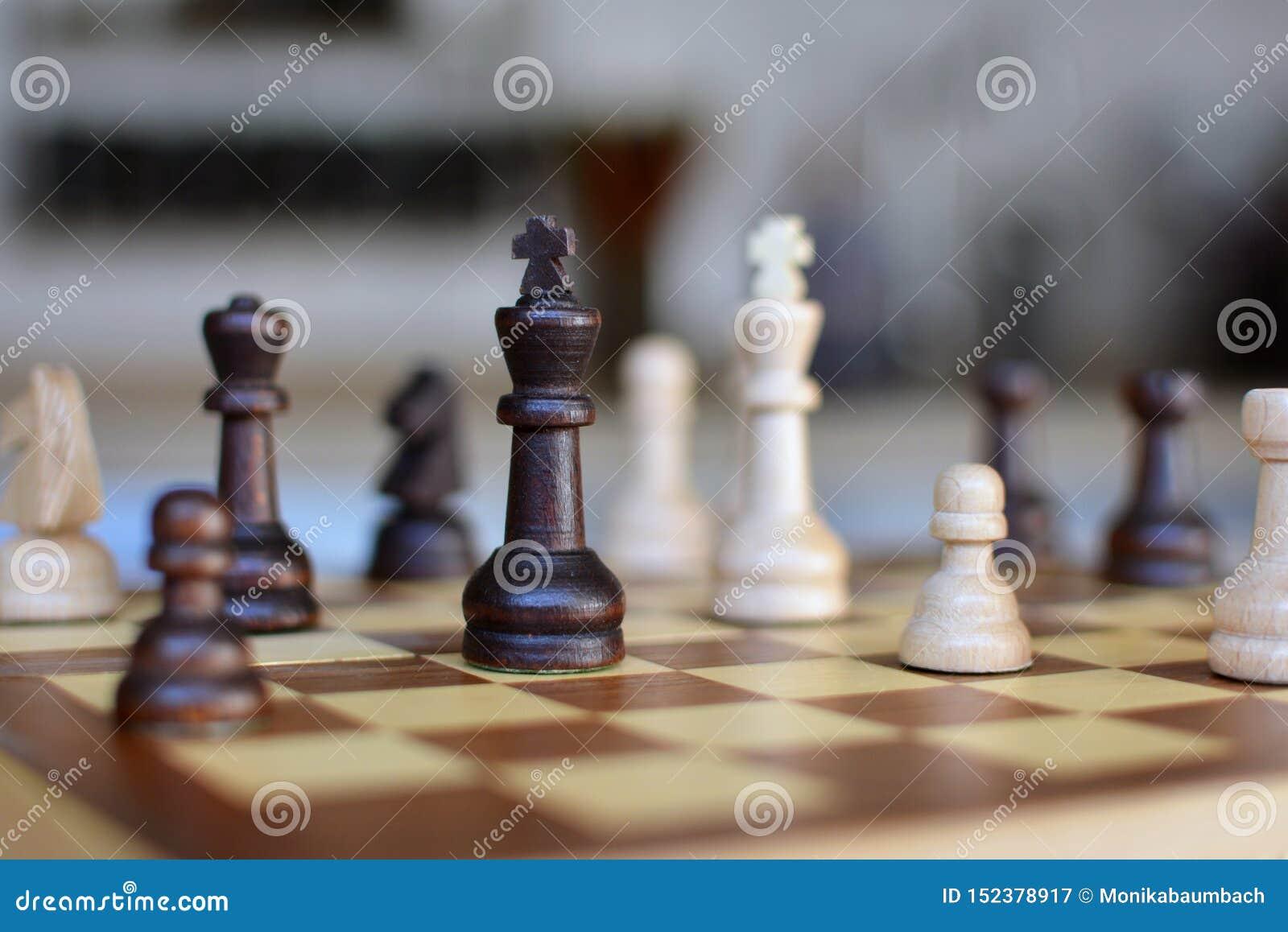 Gioco di scacchiera con il fuoco sui pezzi in bianco e nero della regina su fondo confuso