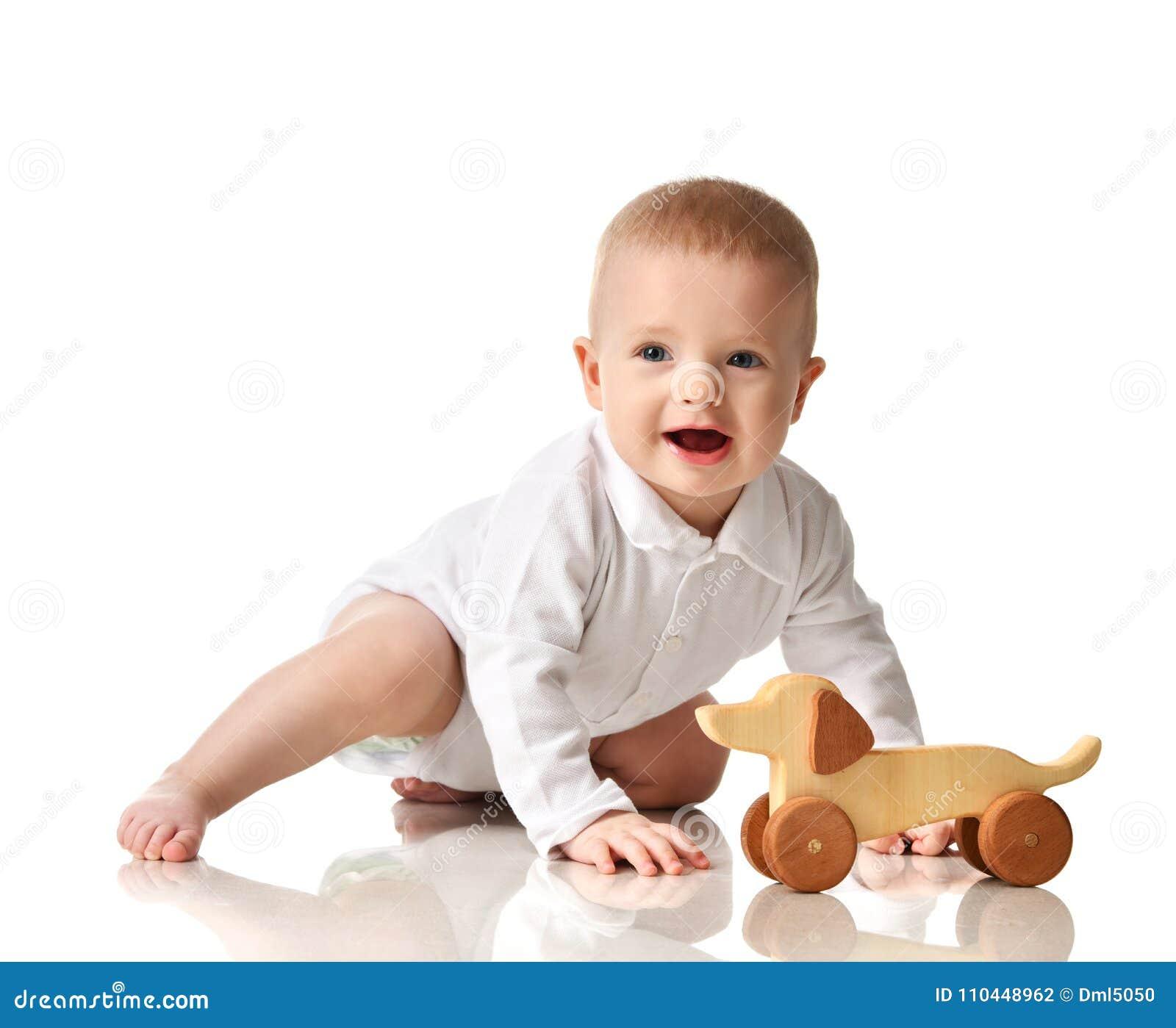 Gioco di seduta del bambino del bambino infantile del neonato con sorridere felice del giocattolo di legno del cane di eco