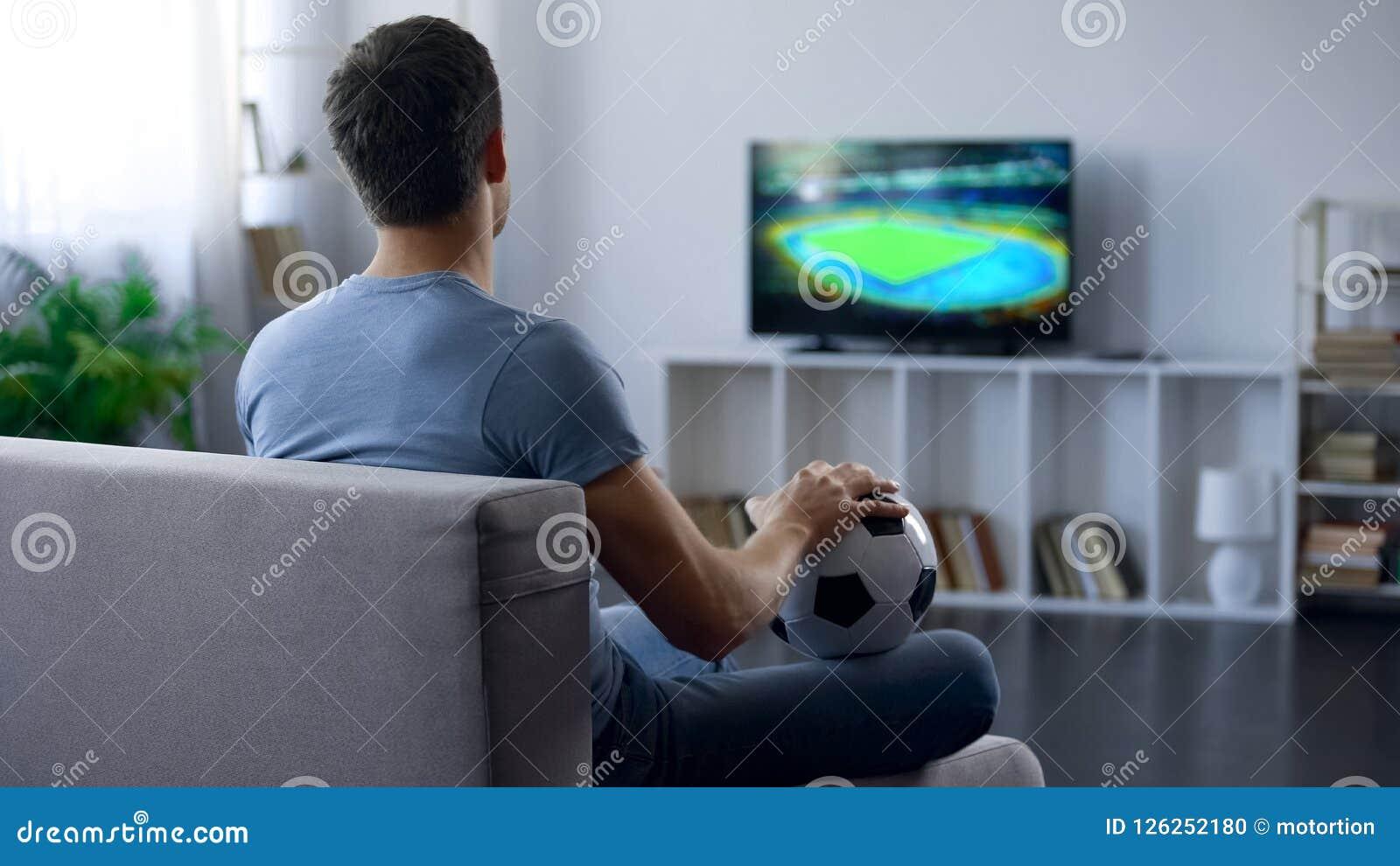 Gioco di sorveglianza dell uomo sulla TV a casa che sostiene uno della squadra di calcio, risultato della partita