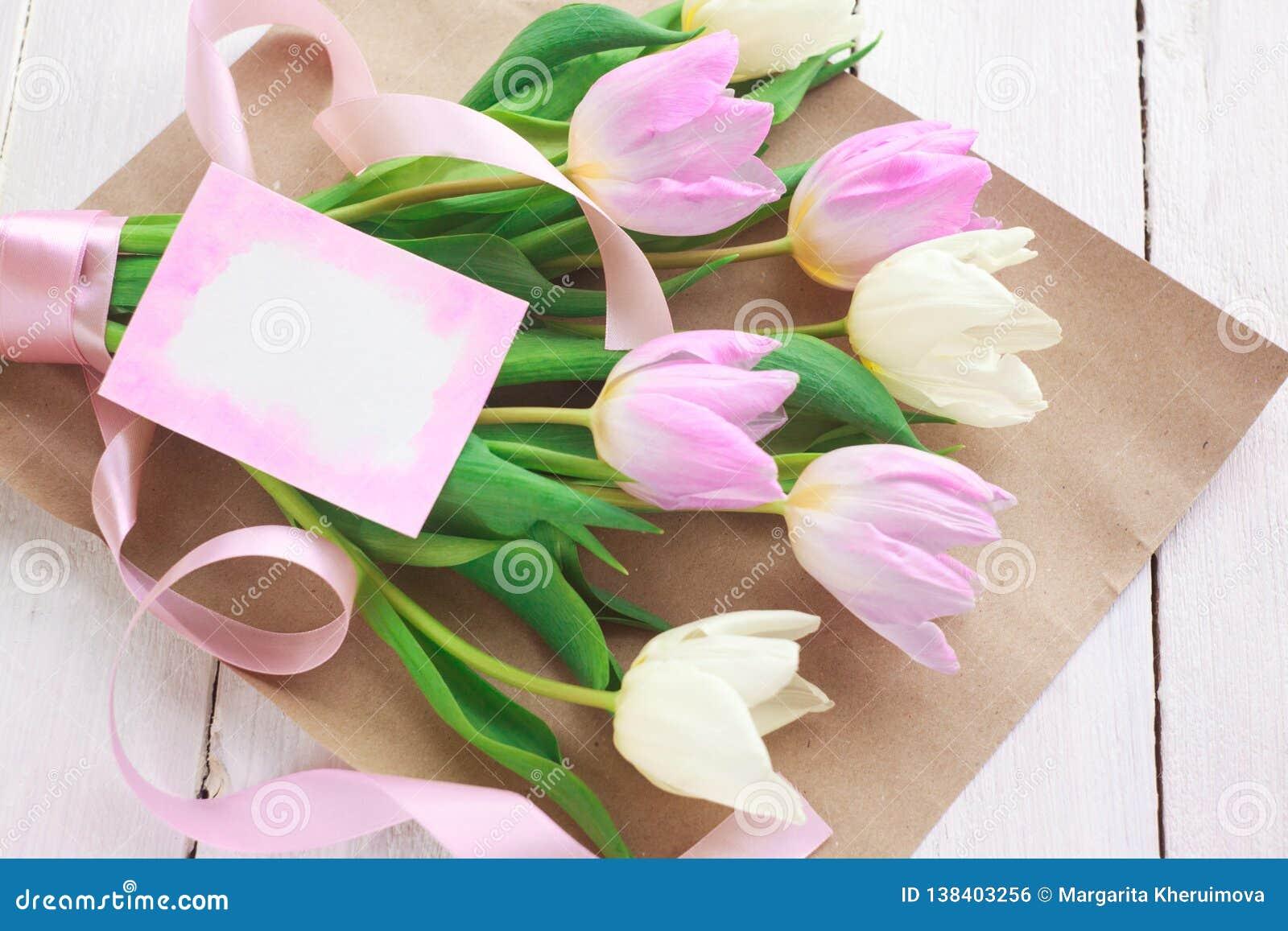 Giorno internazionale del ` s delle donne Un mazzo dei tulipani bianchi e rosa con un nastro su un fondo bianco Cartolina d augur