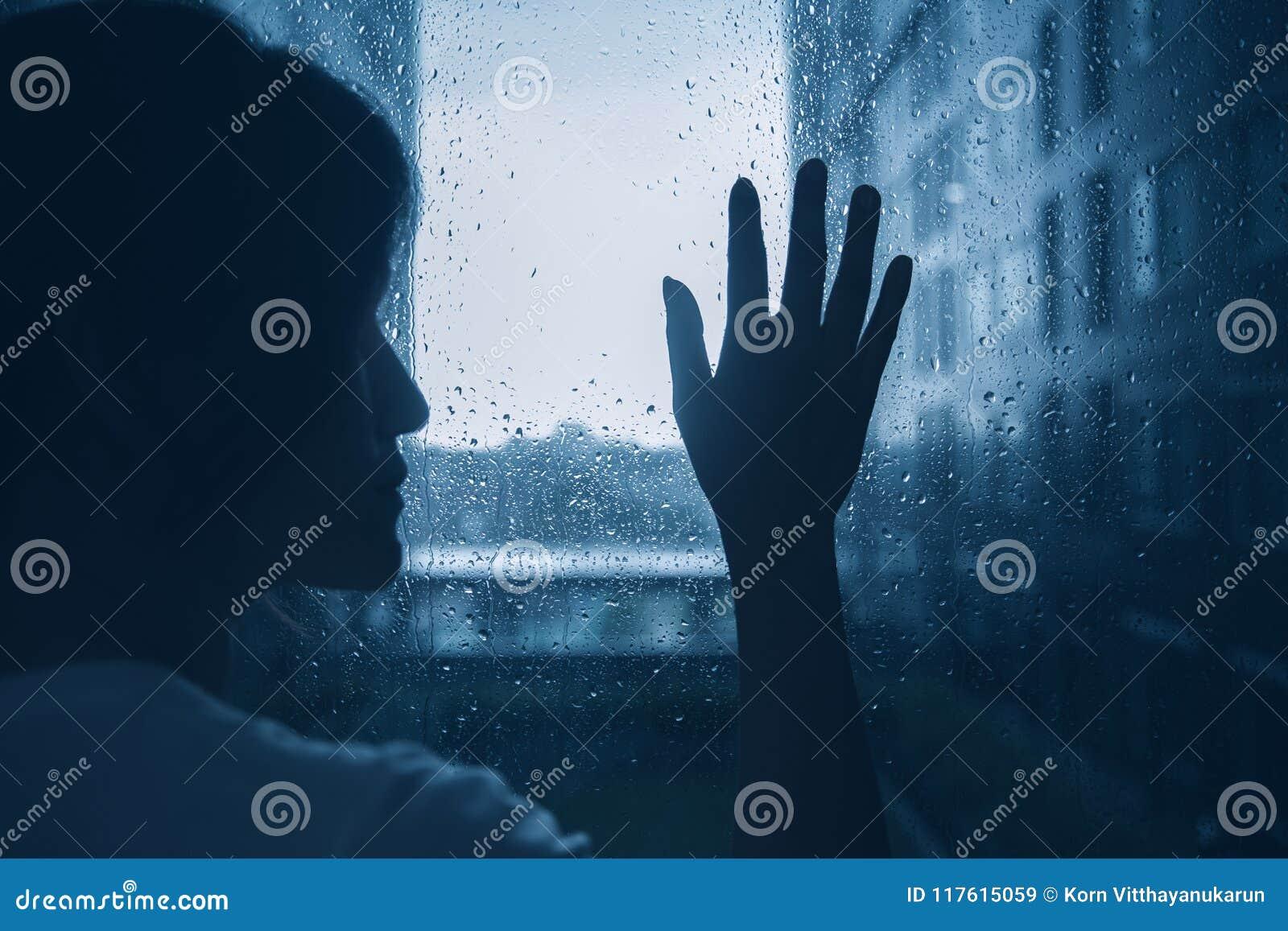Giorno piovoso solo triste delle finestre di vetro di tocco della siluetta della donna di umore di depressione