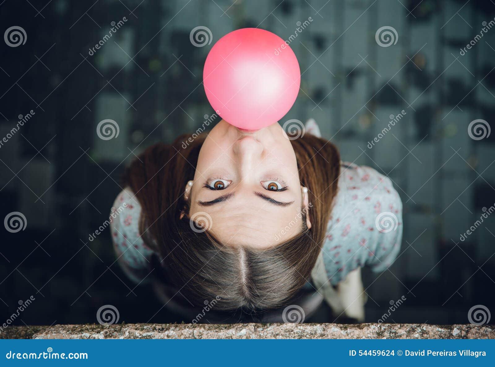 Giovane adolescente che soffia di gomma da masticare rosa