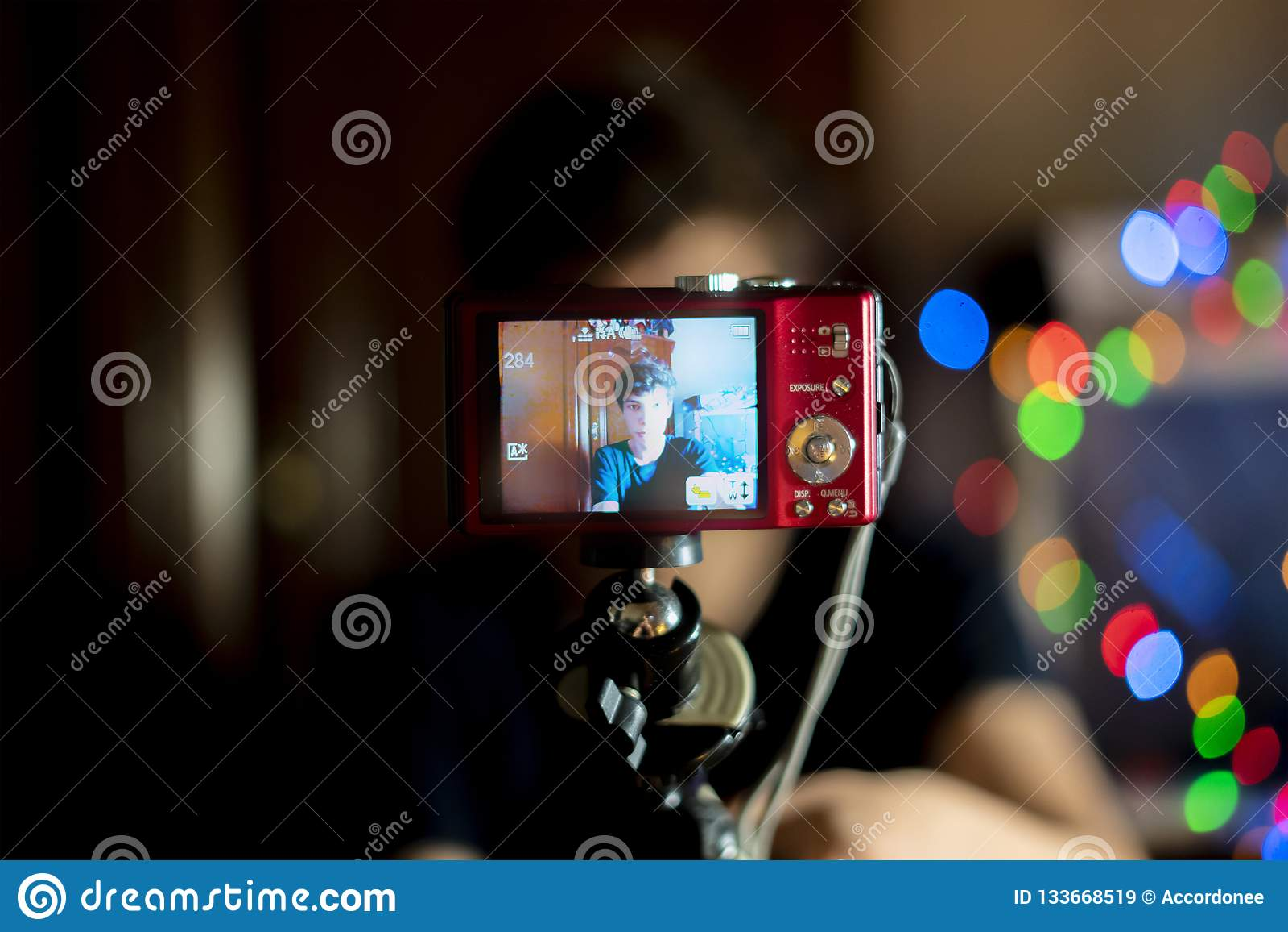 Giovane adolescente maschio che fa un blog con la macchina fotografica a casa, fucilazione f del vlog