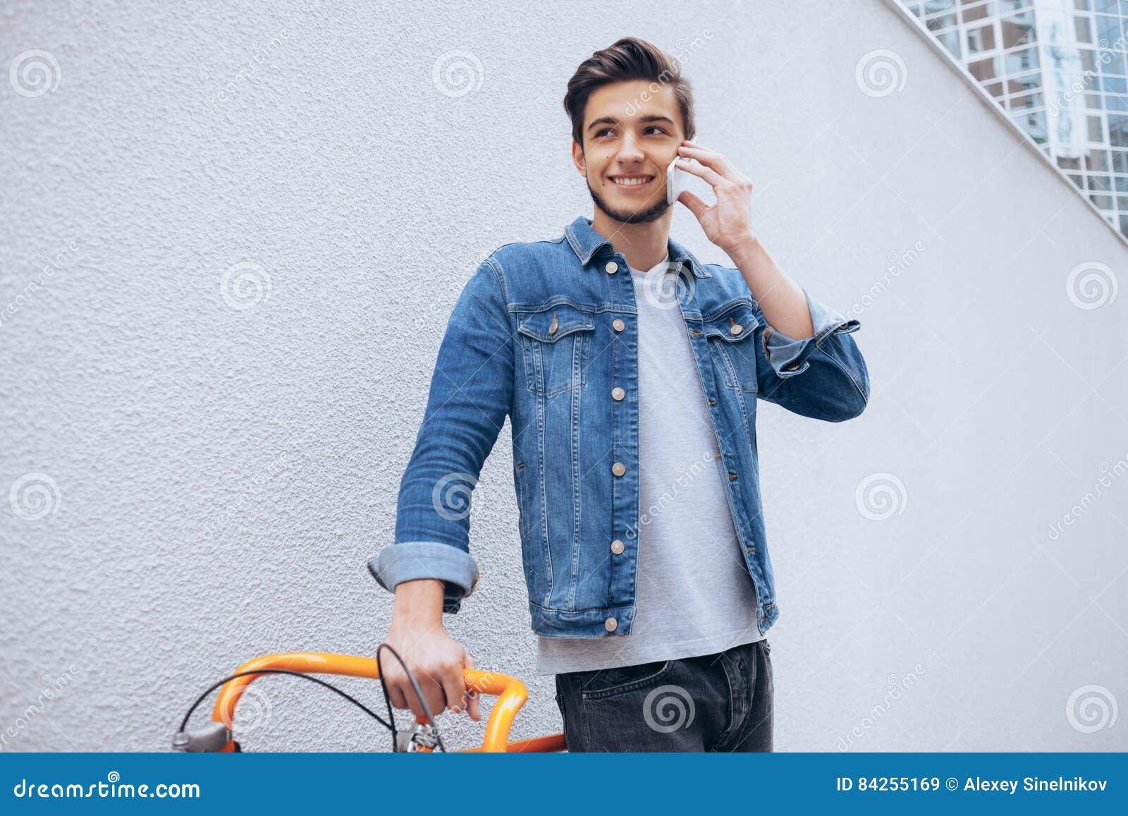 Giovane allegro che parla sul telefono cellulare e che sorride mentre stando vicino alla sua bicicletta