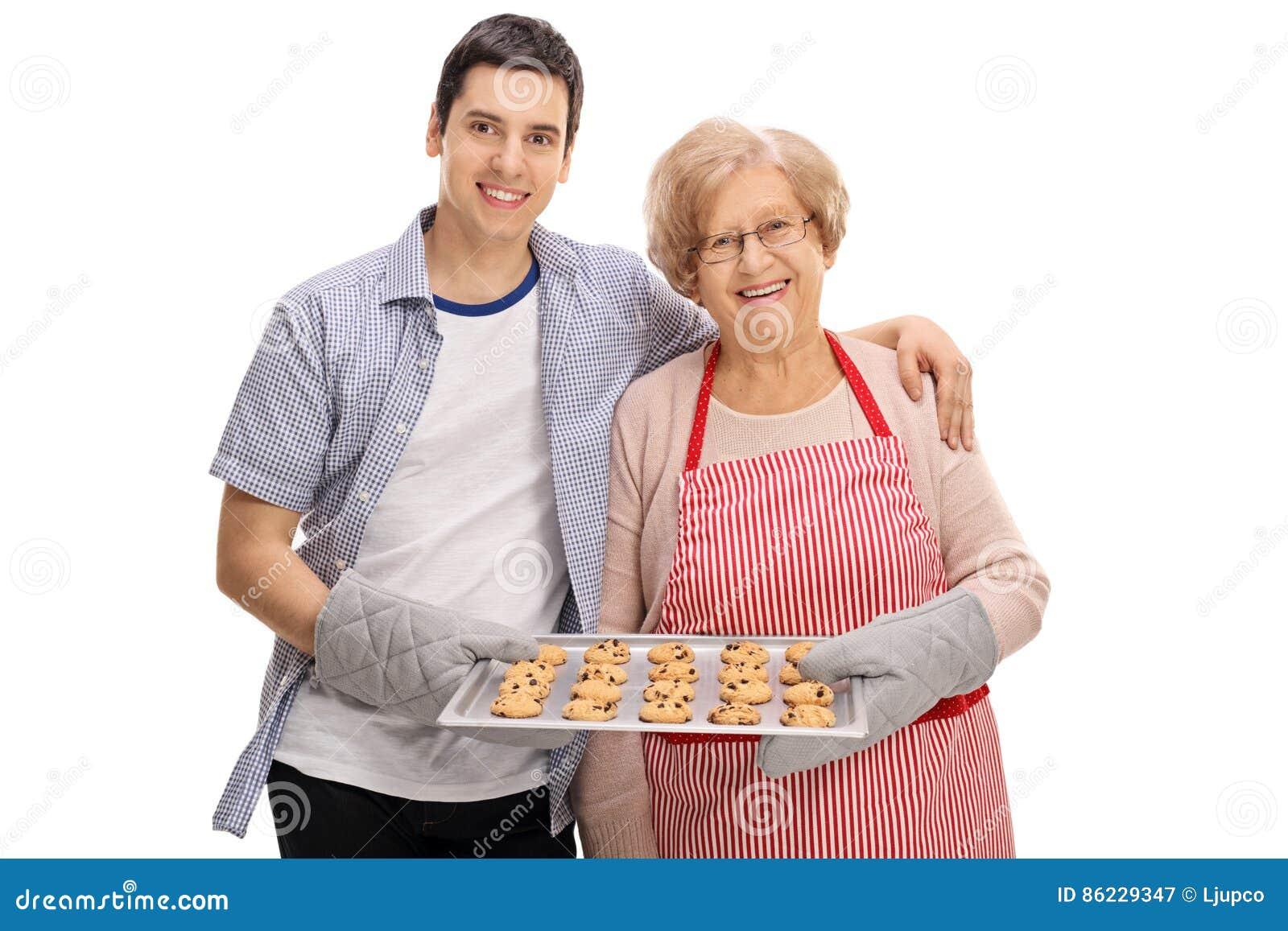 Giovane allegro e vassoio anziano della tenuta di signora di biscotti
