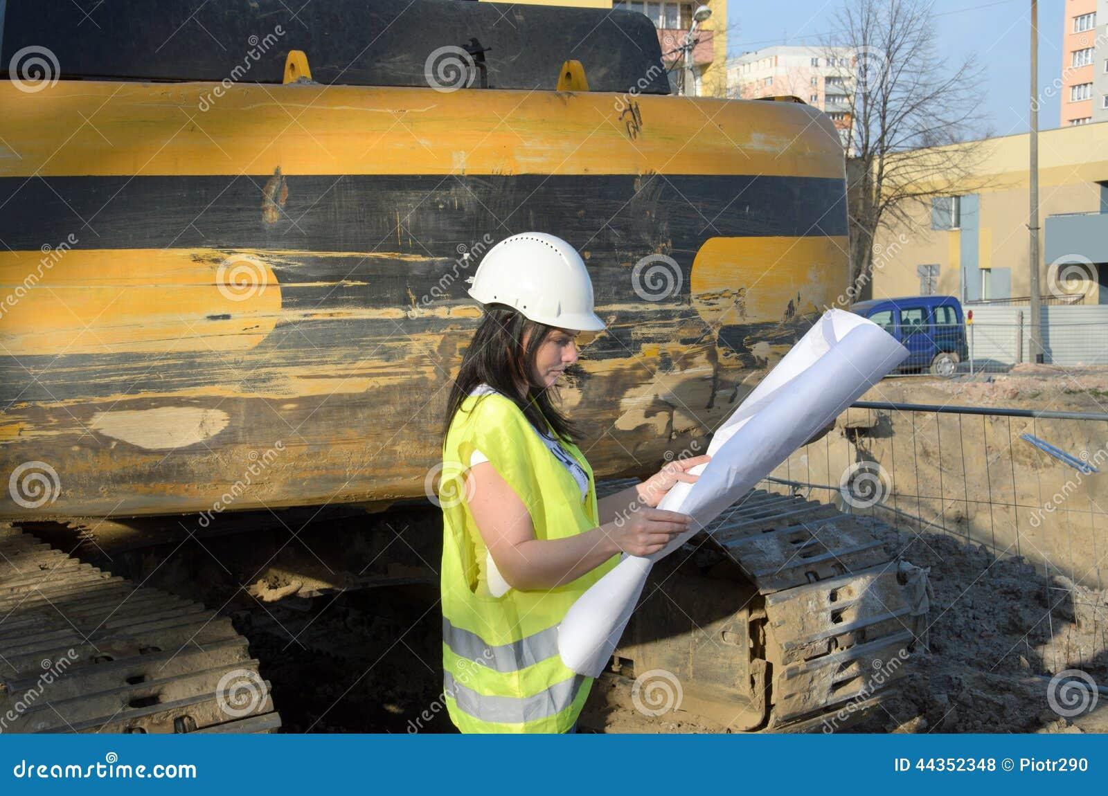 Giovane architetto femminile al cantiere della costruzione