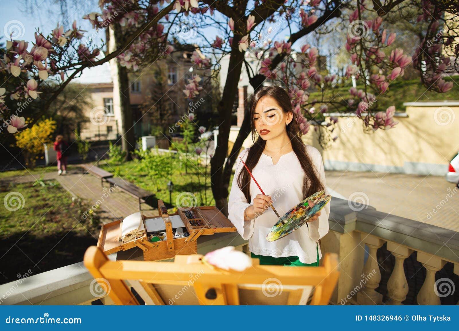 Giovane artista castana della donna che tiene in mani una spazzola e una tavolozza Vicino lei l albero della magnolia e la varia