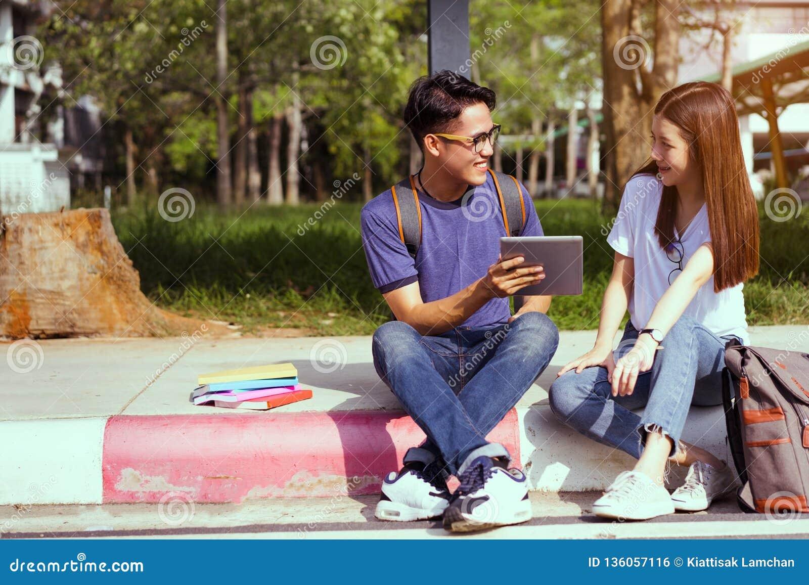 Giovane asiatico degli studenti insieme facendo uso del computer portatile