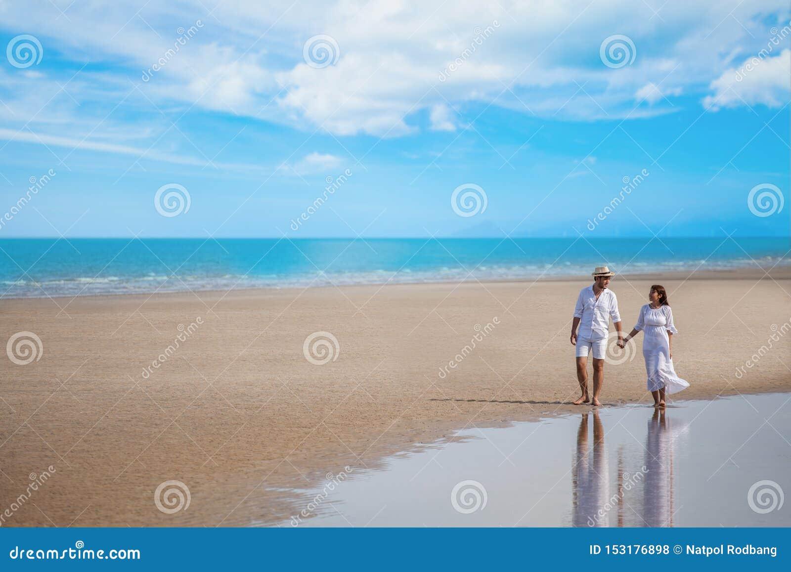 Giovane asiatico delle coppie nell amore che cammina insieme e che tiene mano alla spiaggia del mare su cielo blu nozze sorrident