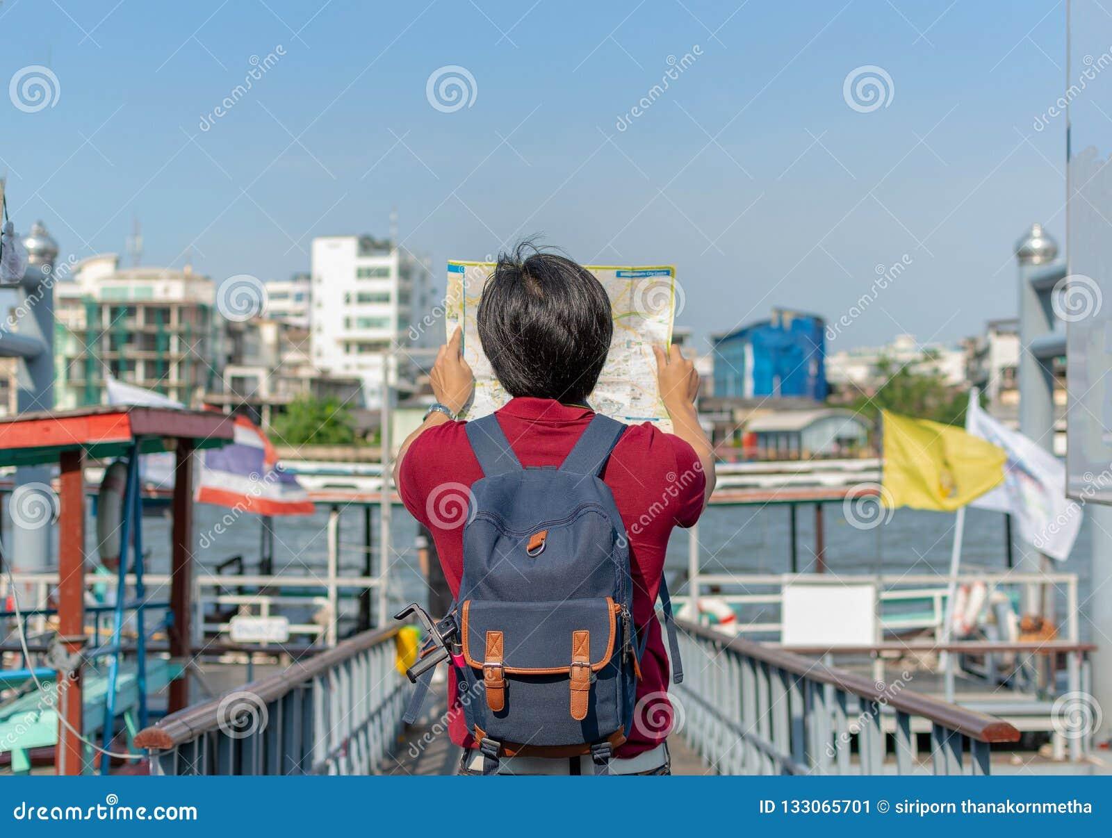 Giovane asiatico dello zaino come turista che esamina il travell della mappa