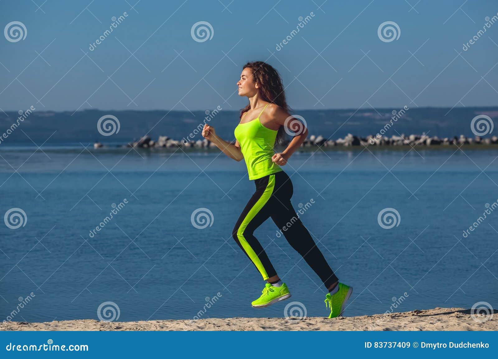 Giovane atleta con capelli ricci, la tuta sportiva verde chiaro e le scarpe da tennis corrente sulla spiaggia di estate, esercizi