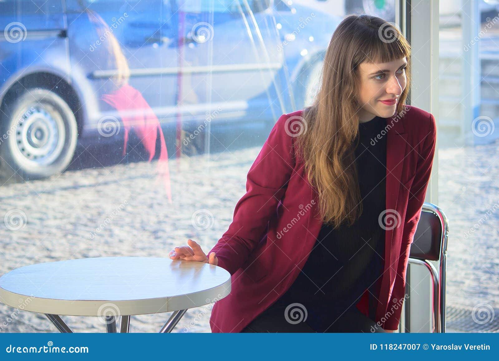 Giovane attesa felice della ragazza dei pantaloni a vita bassa