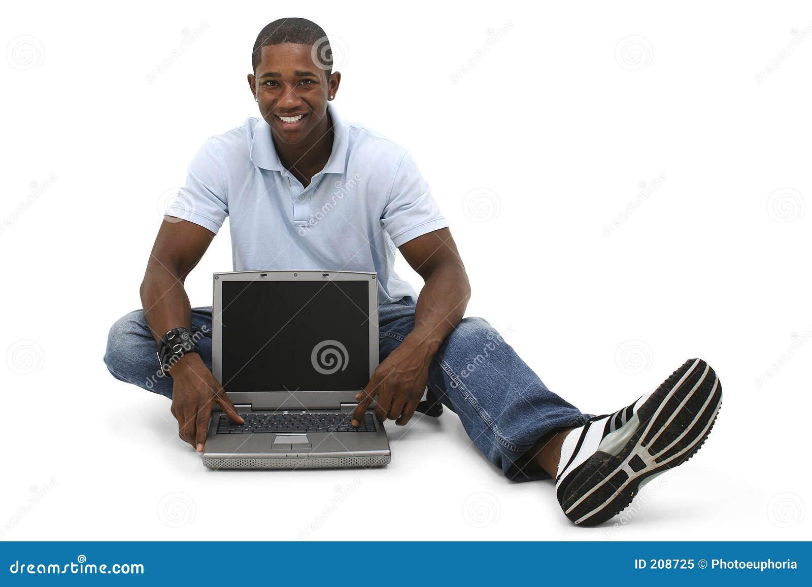 Giovane attraente che si siede sul pavimento con il computer portatile
