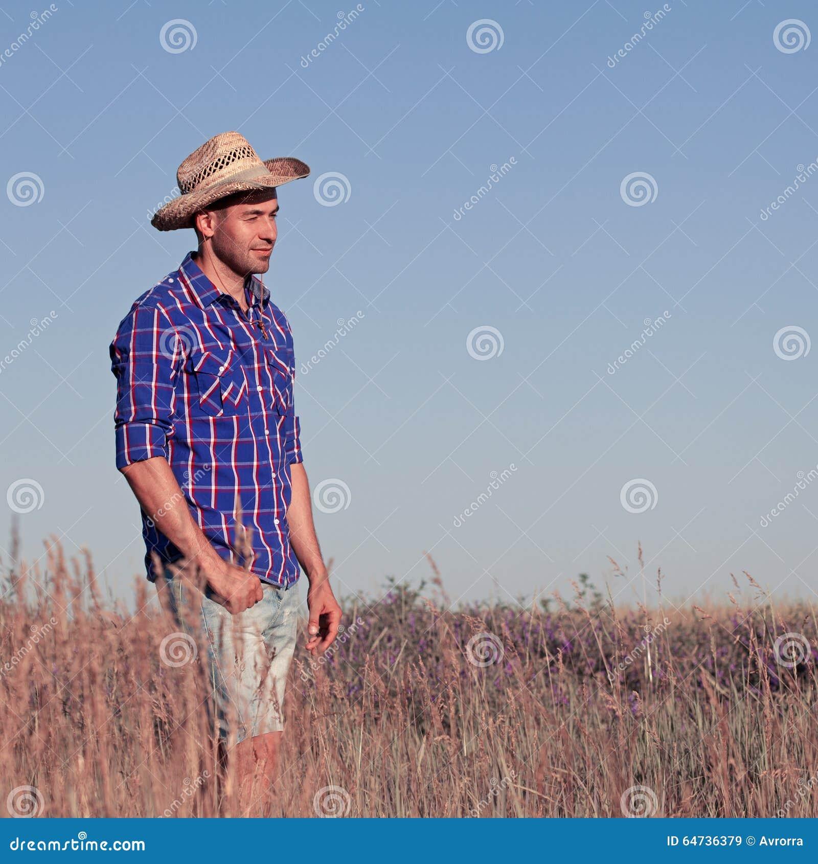 Giovane attraente che sta in un campo cowboy