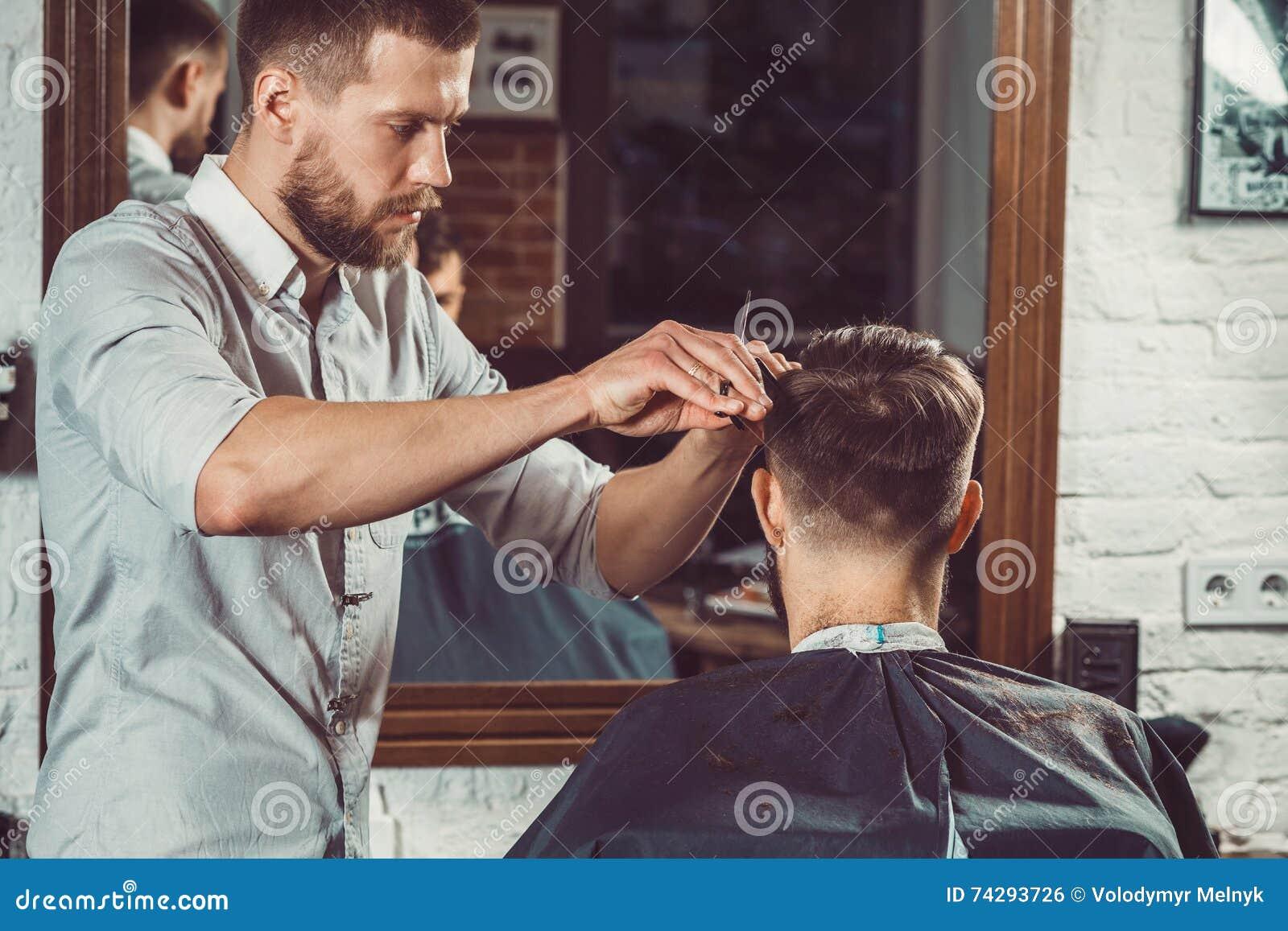 Giovane barbiere bello che fa taglio di capelli dell uomo attraente in parrucchiere