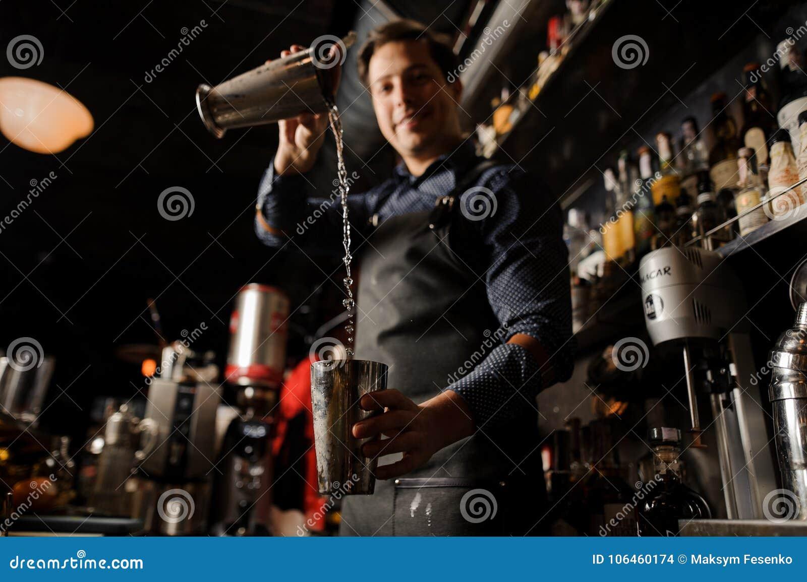 Giovane barista sorridente che versa bevanda alcolica da un vetro del metallo in un altro