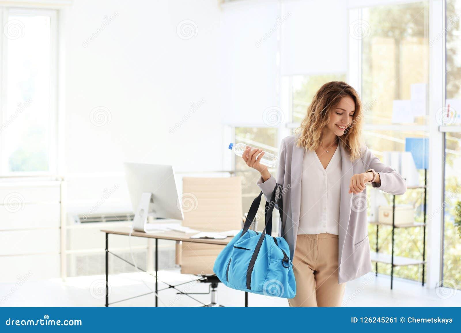 Giovane bella borsa di forma fisica della tenuta della donna di affari in ufficio