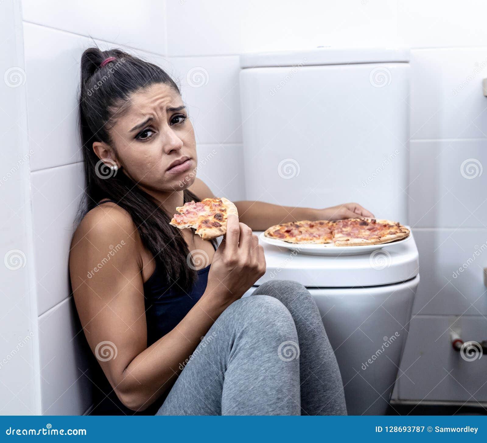 Giovane bella donna affetta da bulimia che si siede sul pavimento del bagno che mangia pizza che sembra colpevole