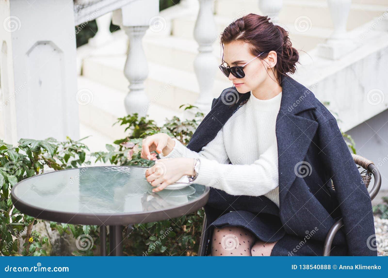 Giovane bella donna alla moda in occhiali da sole che si siedono in un caffè bevente all aperto del caffè