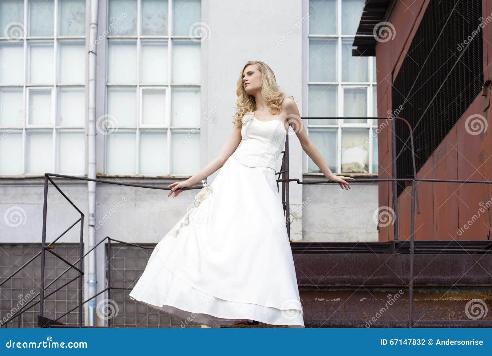 Giovane bella donna bionda in vestito nuziale