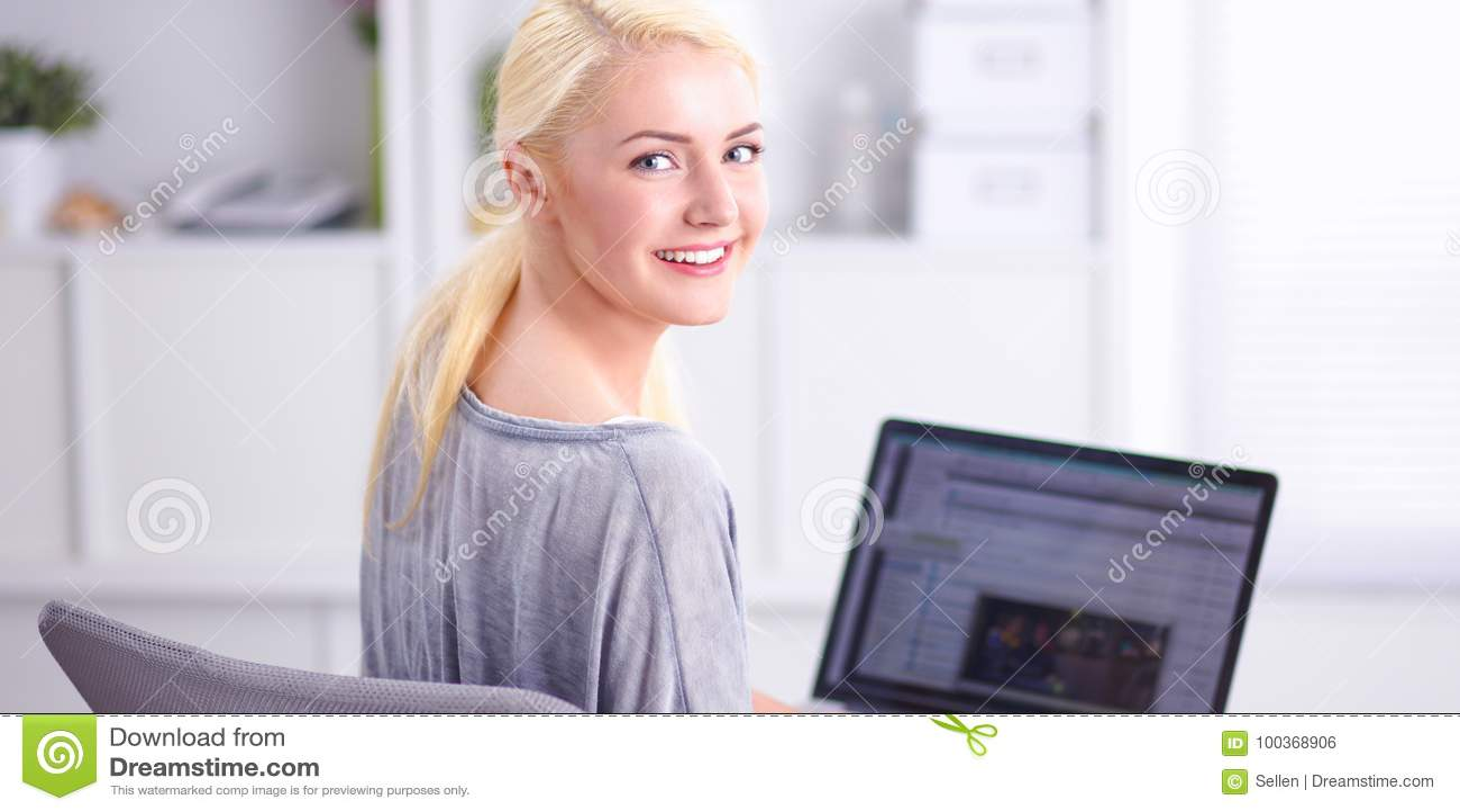 Giovane bella donna che per mezzo di un computer portatile a casa
