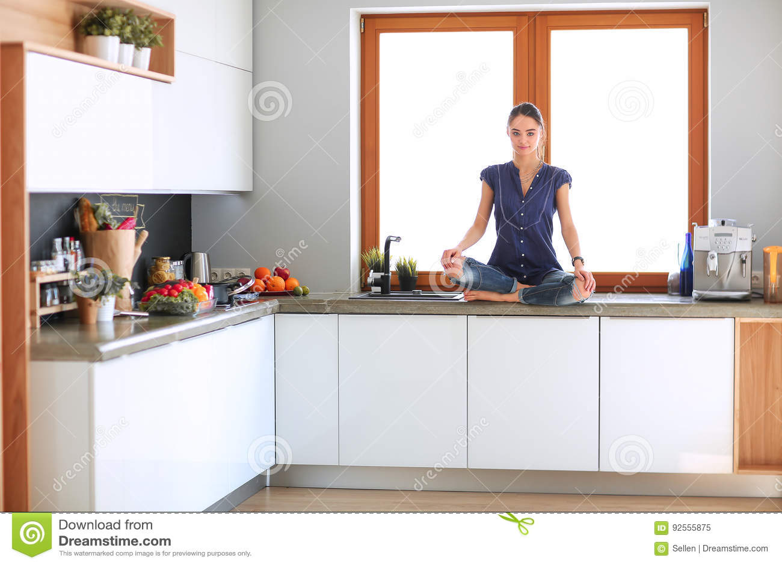 Giovane bella donna che si siede al tavolo da cucina nella posizione di loto