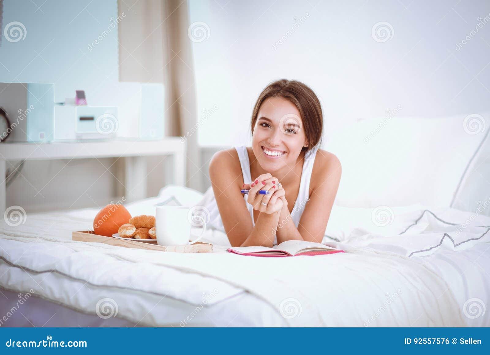 Giovane bella donna che si siede a letto e che scrive in un quaderno