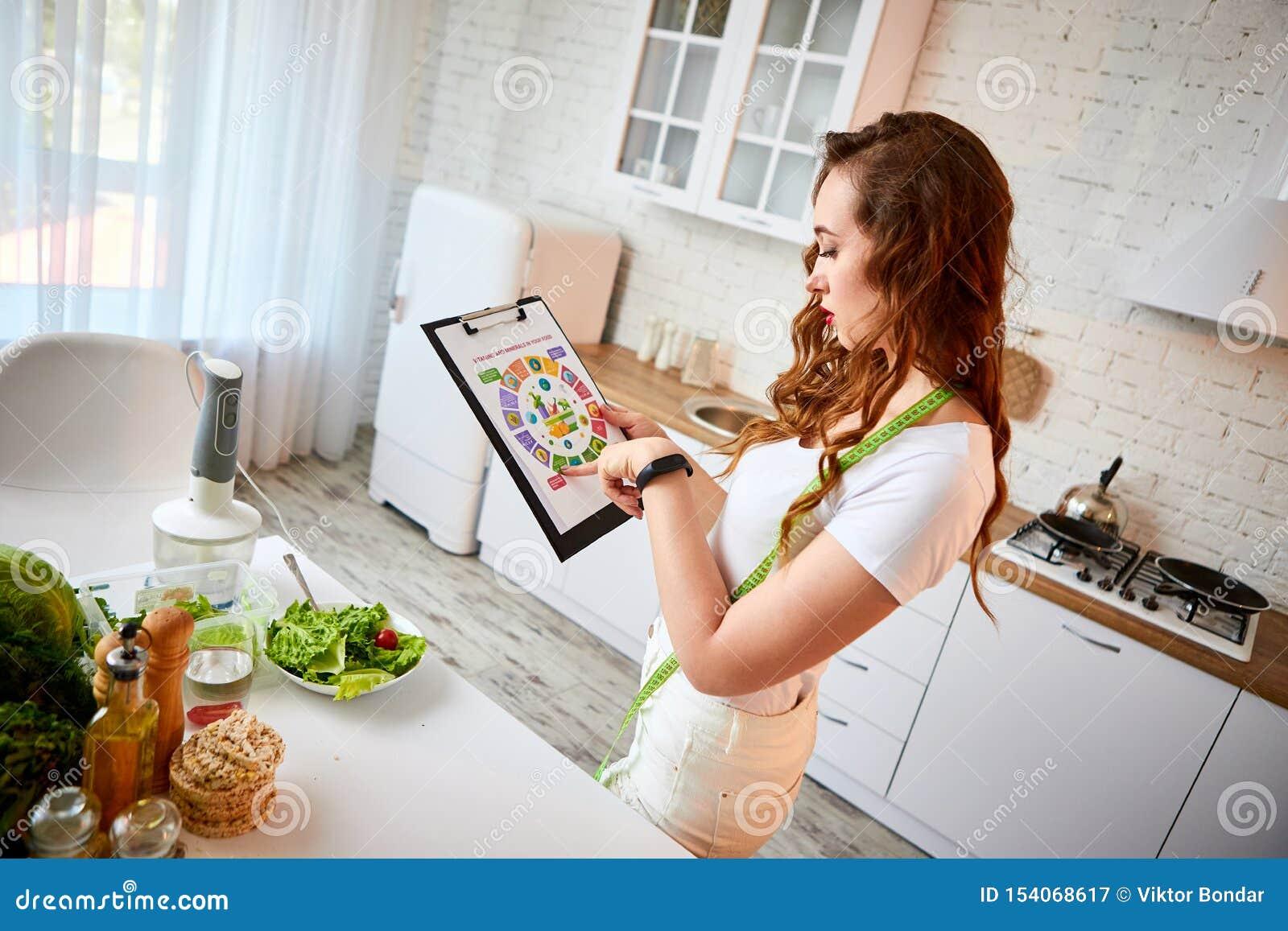 Giovane bella donna che utilizza compressa con attimo infographic che cucina nella cucina moderna Cibo sano, vitamine, stanti a d