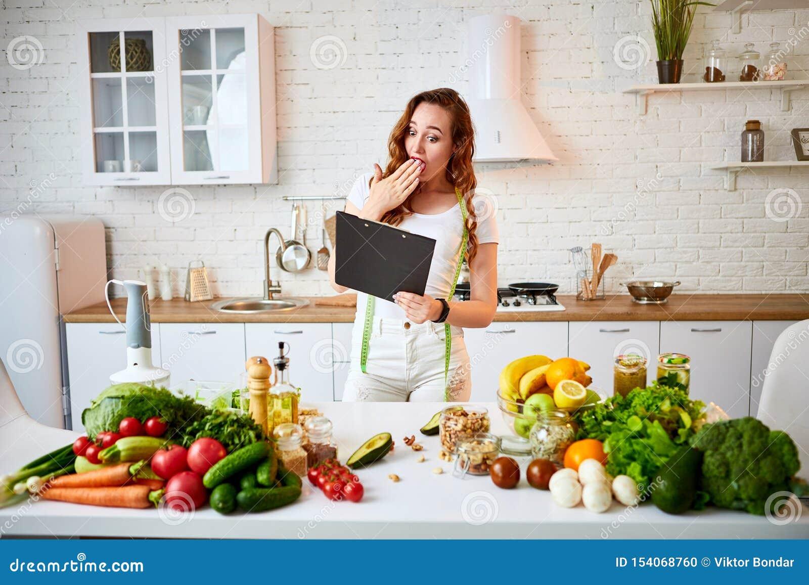 Giovane bella donna che utilizza compressa mentre cucinando nella cucina moderna Cibo sano, vitamine, essere a dieta, tecnologia