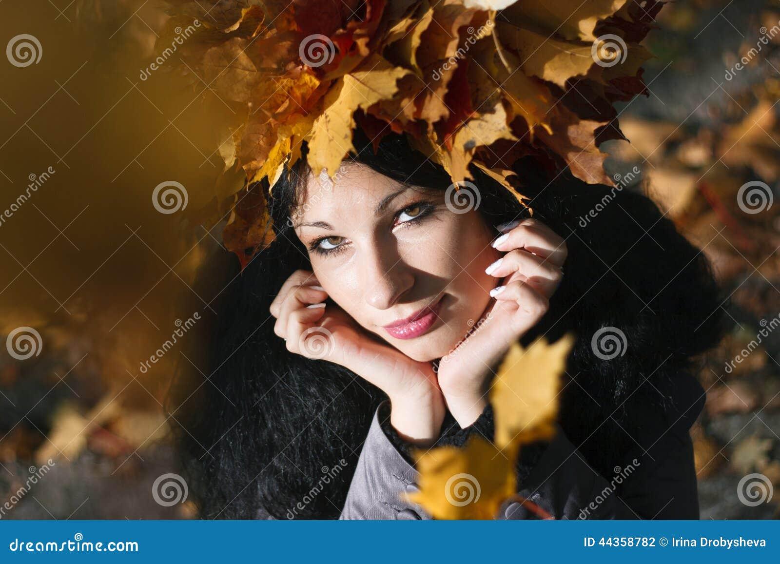 Giovane bella donna con le foglie di autunno della corona