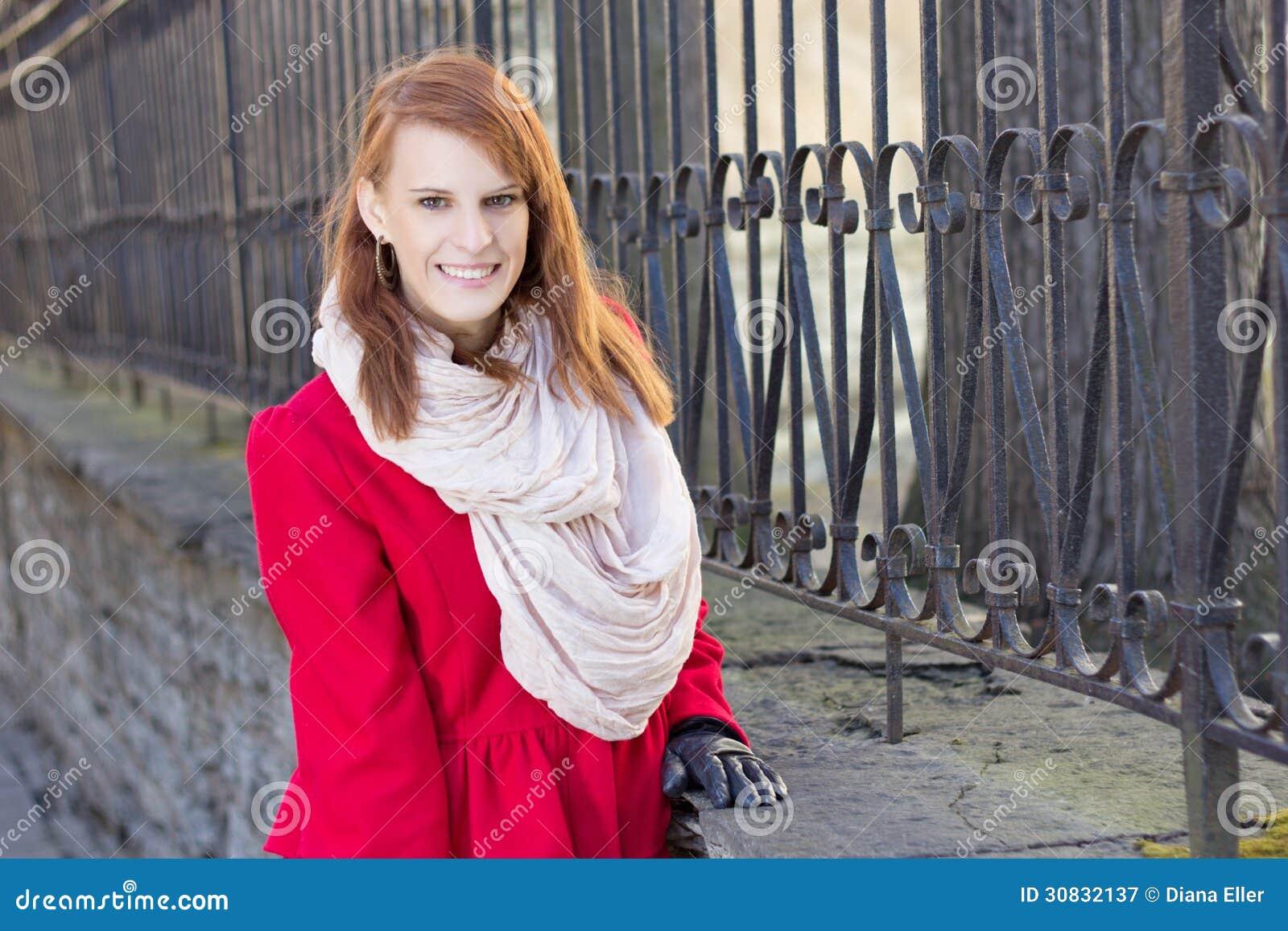 Giovane bella donna dai capelli rossi che posa vicino al recinto del metall