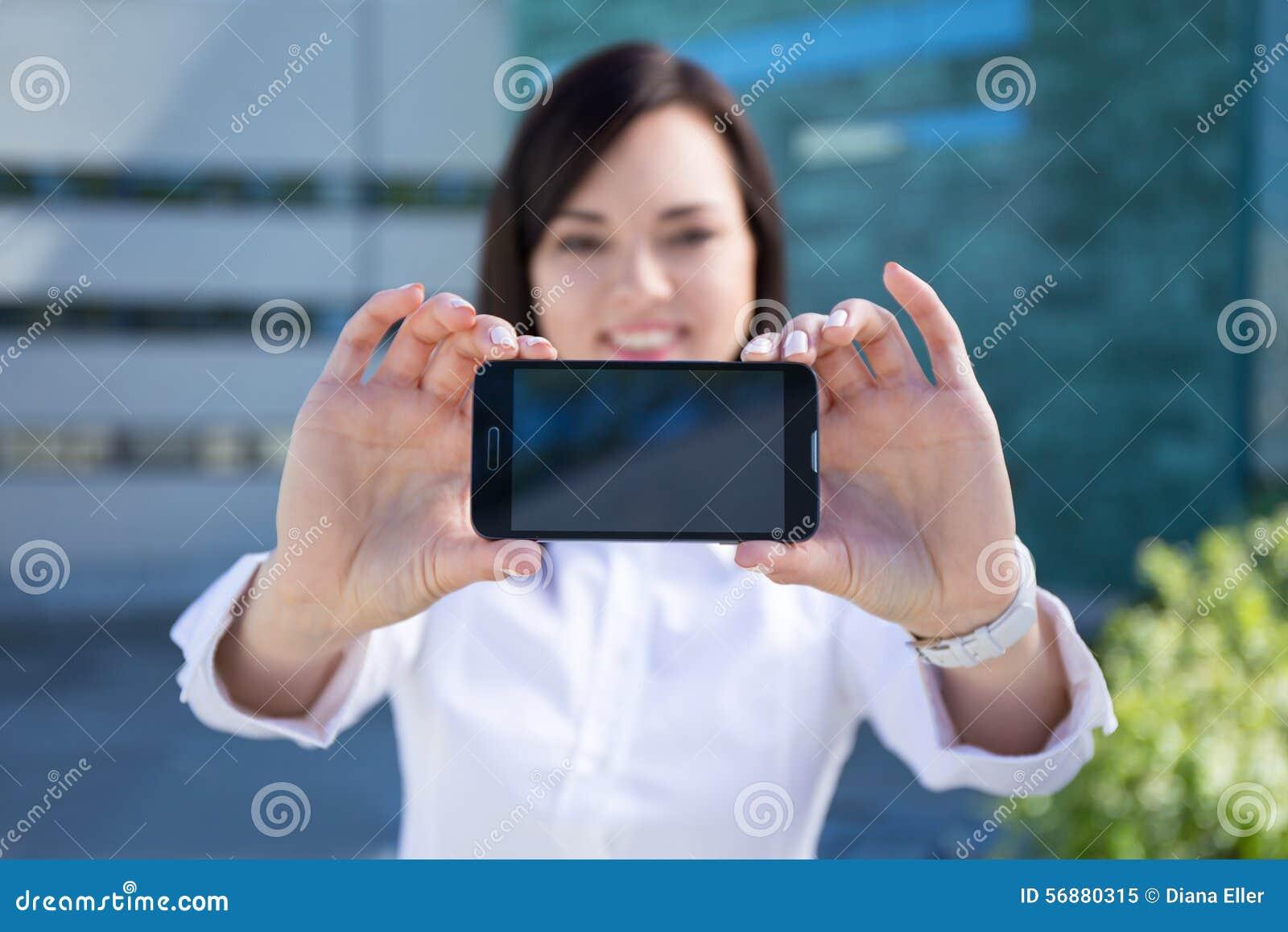 Giovane bella donna di affari che mostra smartphone con l SCR in bianco