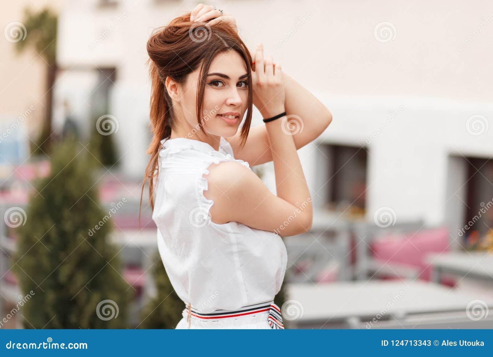 77ab210ab453 Giovane bella giovane donna felice con un sorriso in un vestito bianco che cammina  nella città