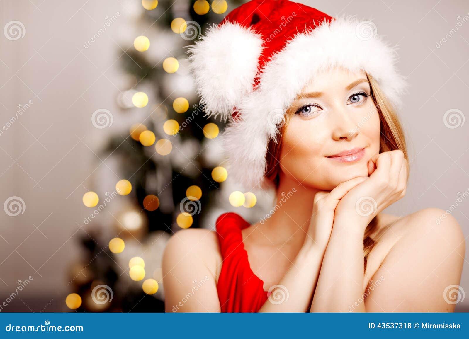 Giovane bella donna sorridente di Santa vicino all albero di Natale Fas