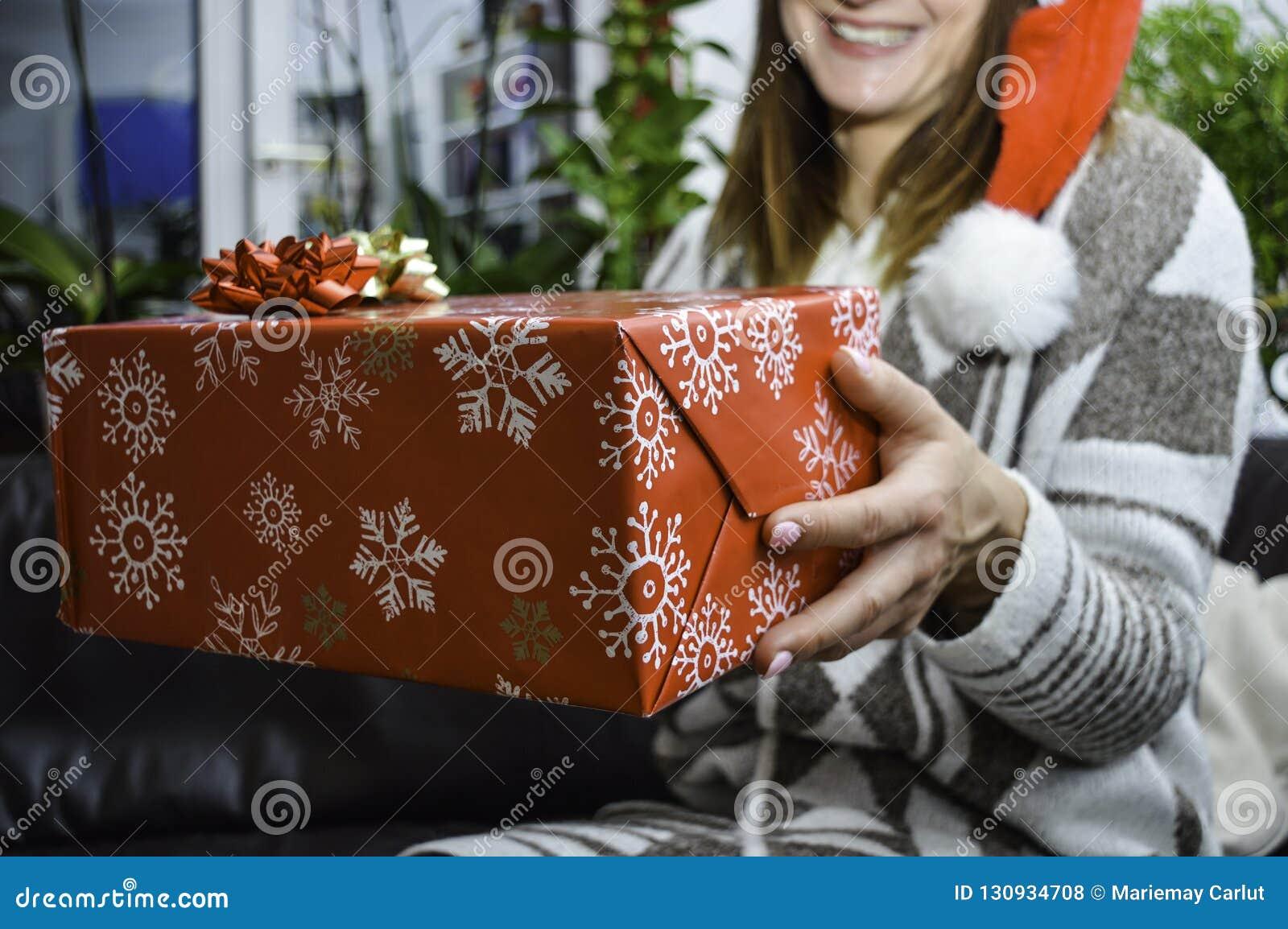 Giovane bella donna sorridente felice che tiene e che dà un regalo di Natale