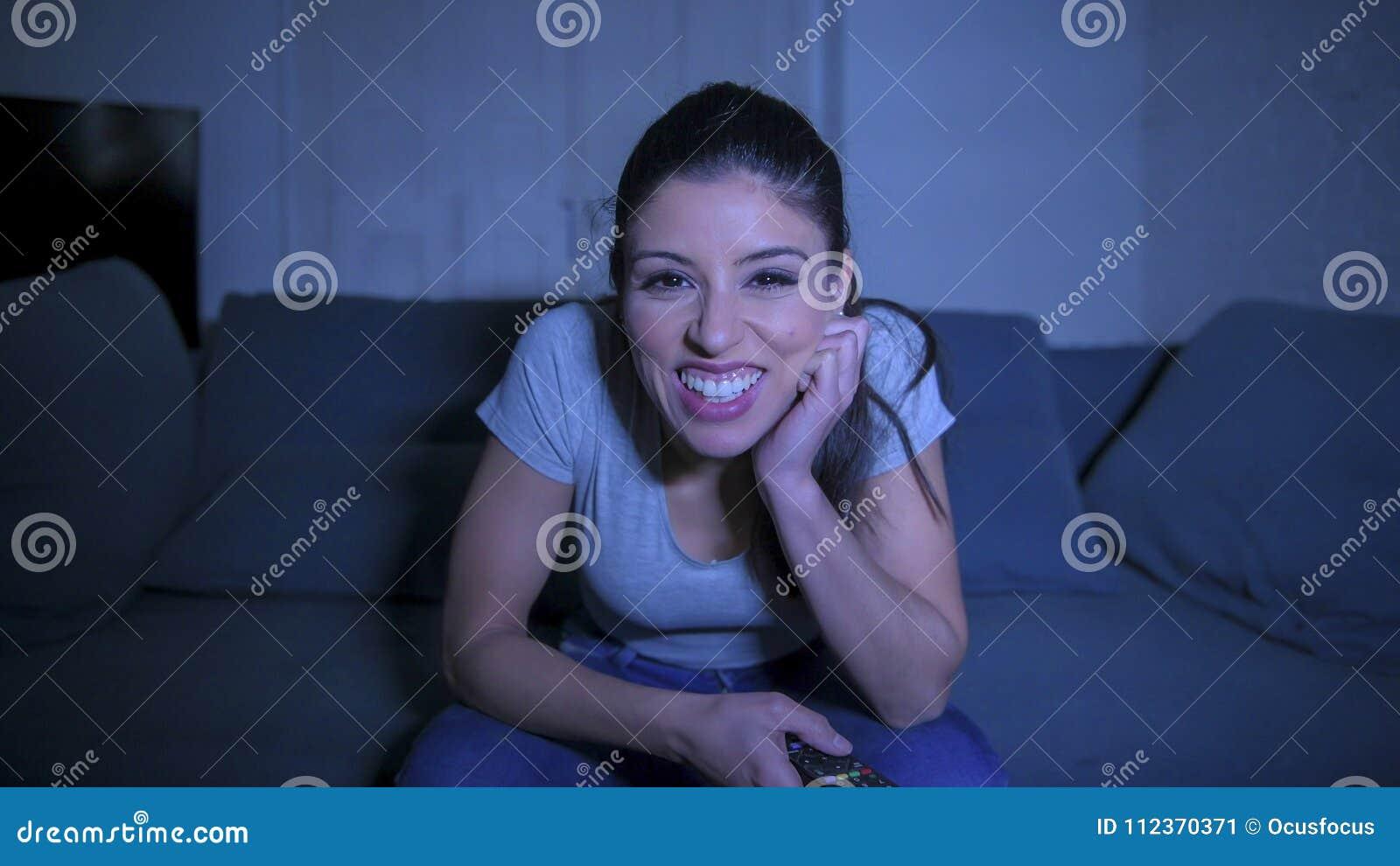 Giovane bella e donna ispanica felice sul suo 30s che tiene la ripresa esterna della TV che gode a casa della televisione di sorv