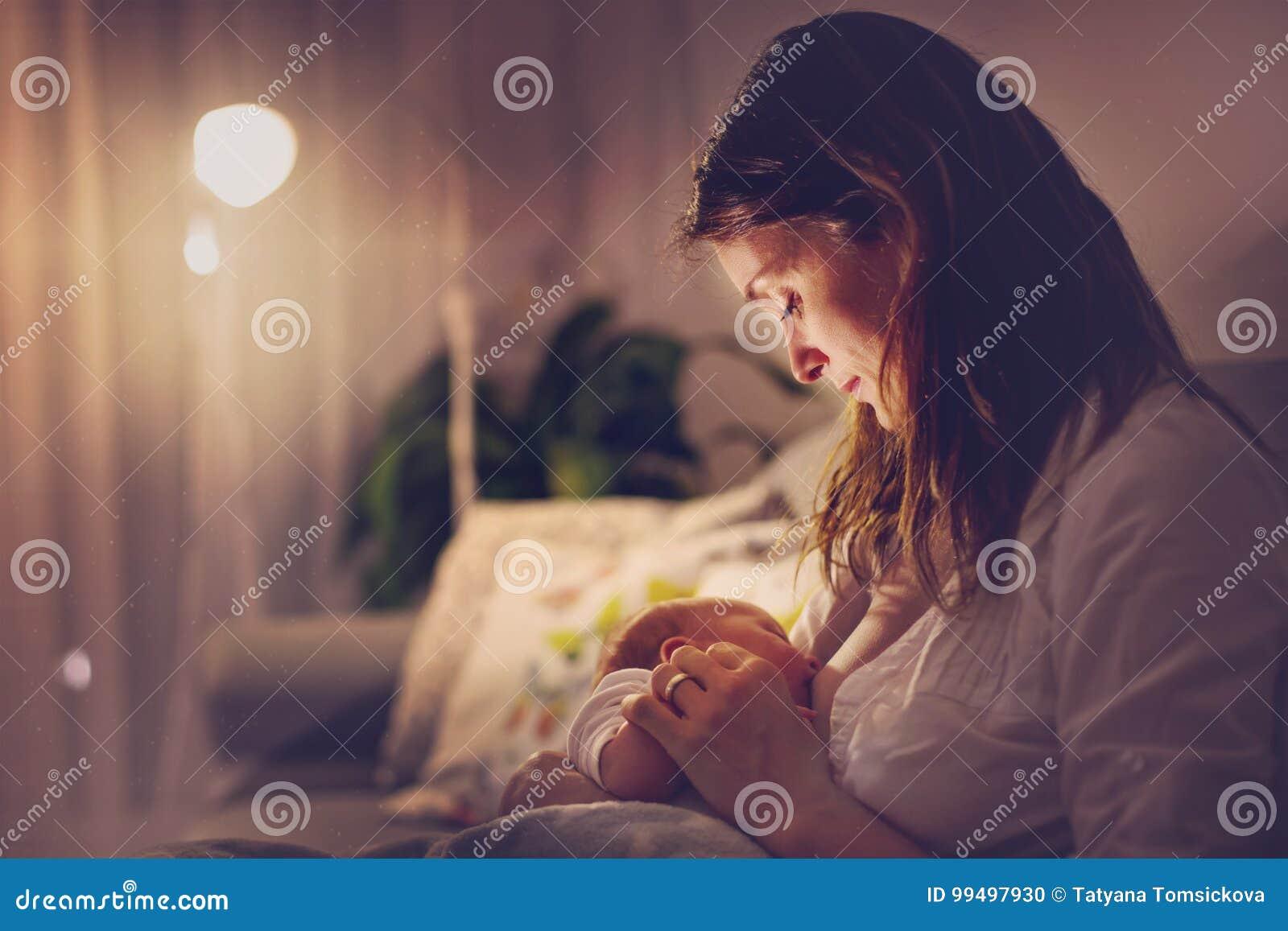 Giovane bella madre, allattante al seno il suo ragazzo di neonato al Ni