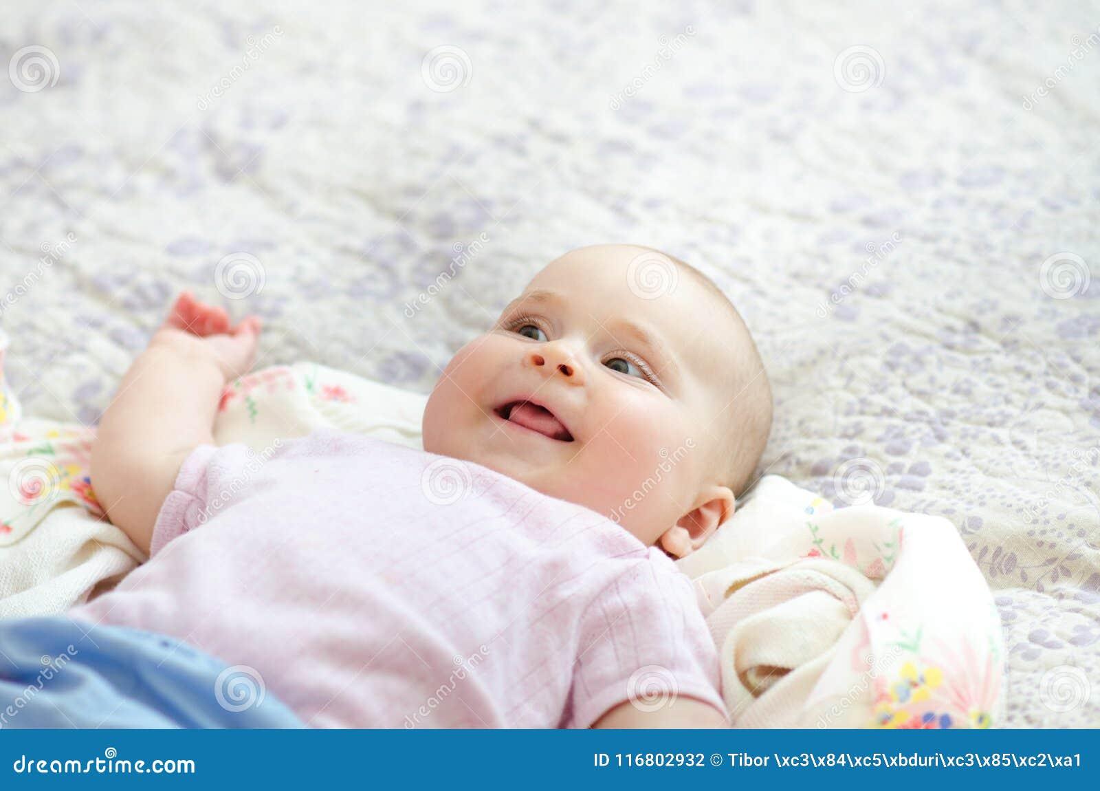 Giovane bella, ragazza adorabile che si trova su un letto con fondo bianco Il genitore ed il bambino sono ridenti e giocanti insi