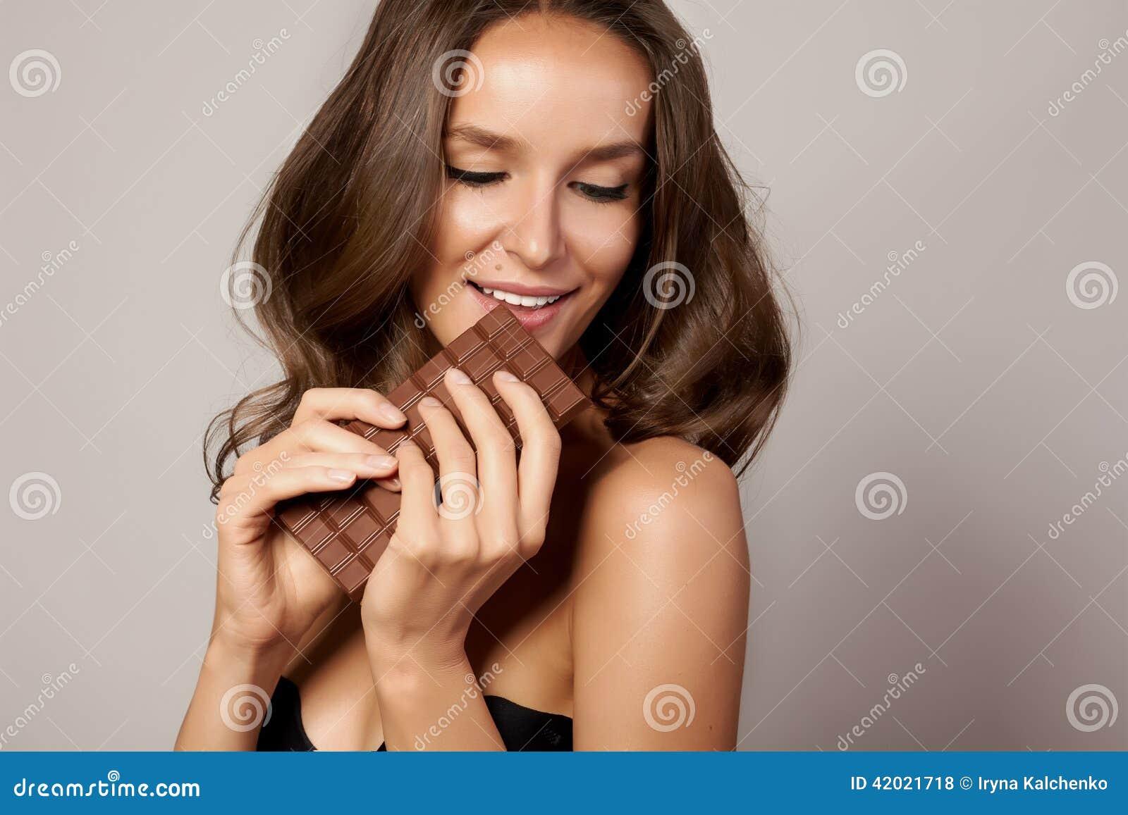 Giovane bella ragazza con capelli ricci scuri, le spalle nude ed il collo, tenenti una barra di cioccolato per godere del gusto e