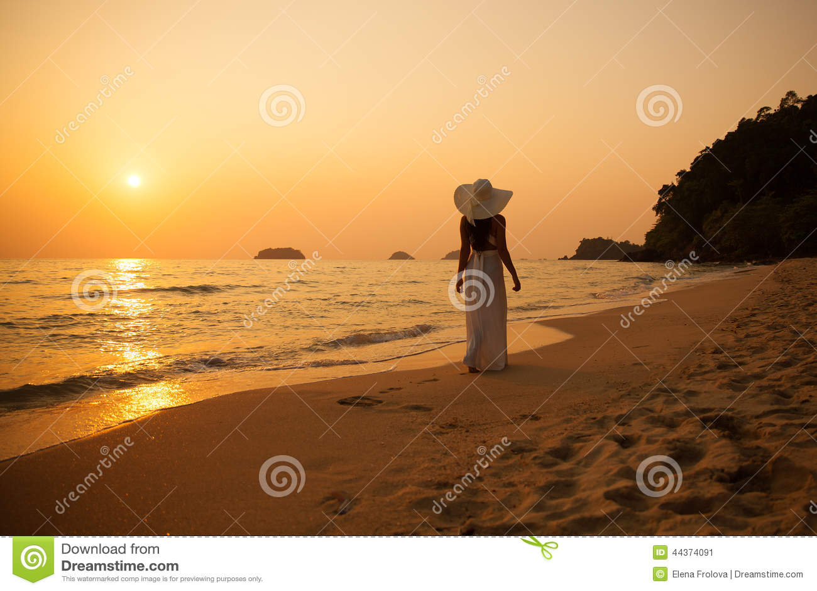 Giovane bella ragazza in un cappello bianco di paglia e del vestito su un tropica