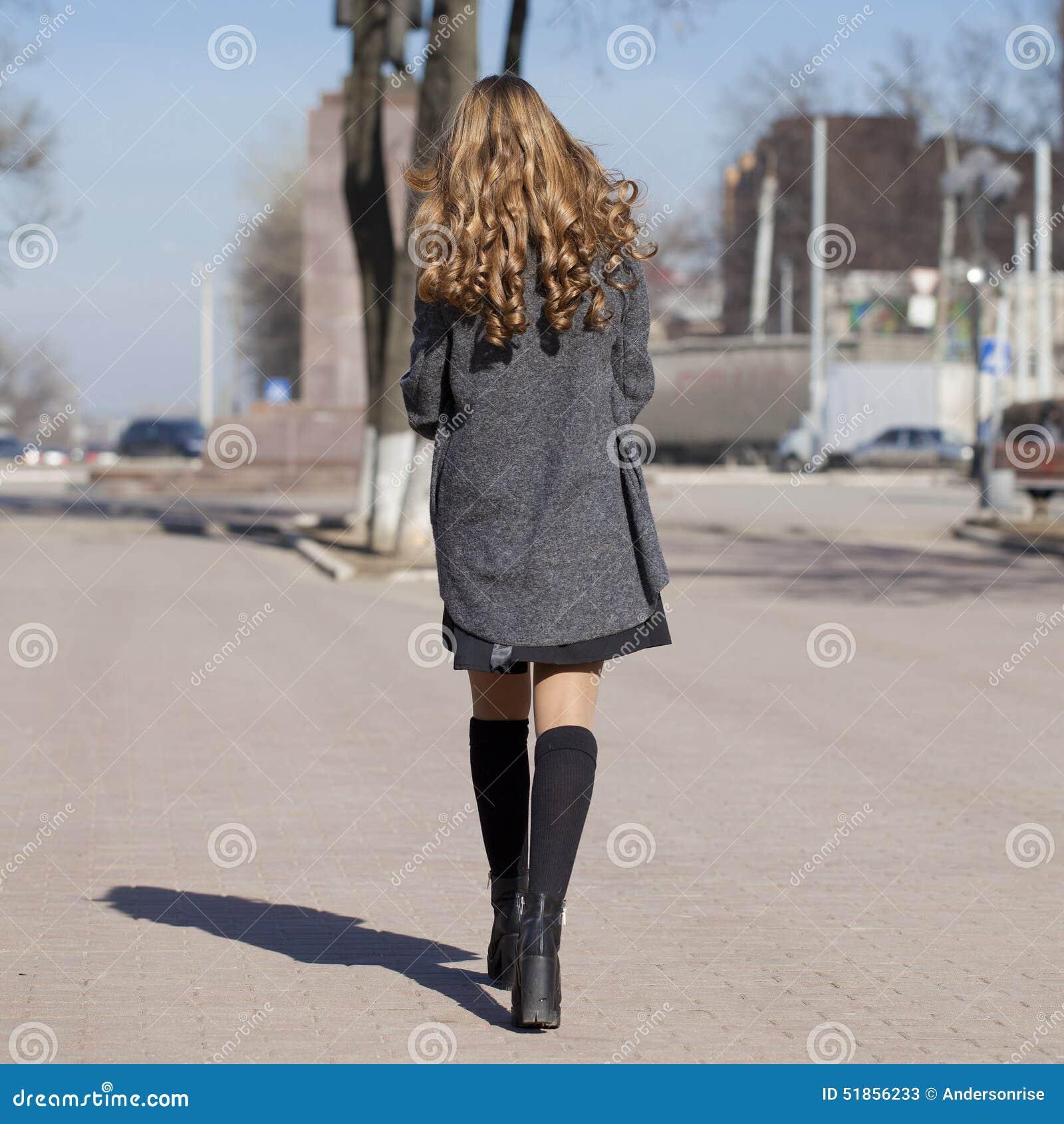 Giovane bella ragazza in un cappotto grigio