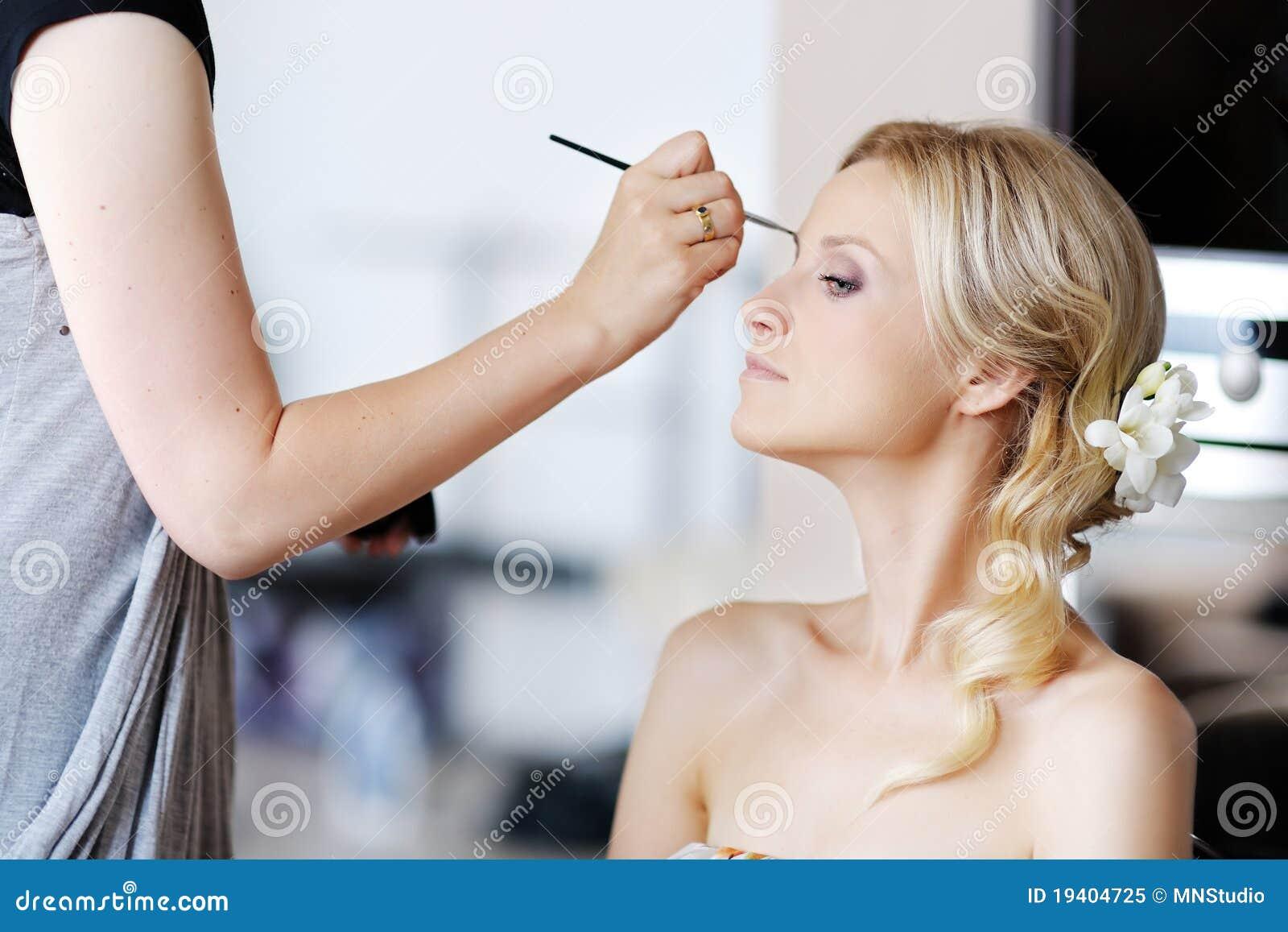Giovane bella sposa che applica trucco di cerimonia nuziale
